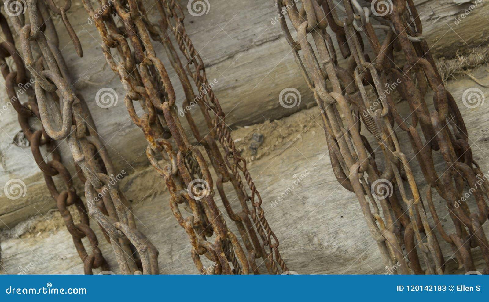 De oude kettingen hangen op een houten logboekmuur