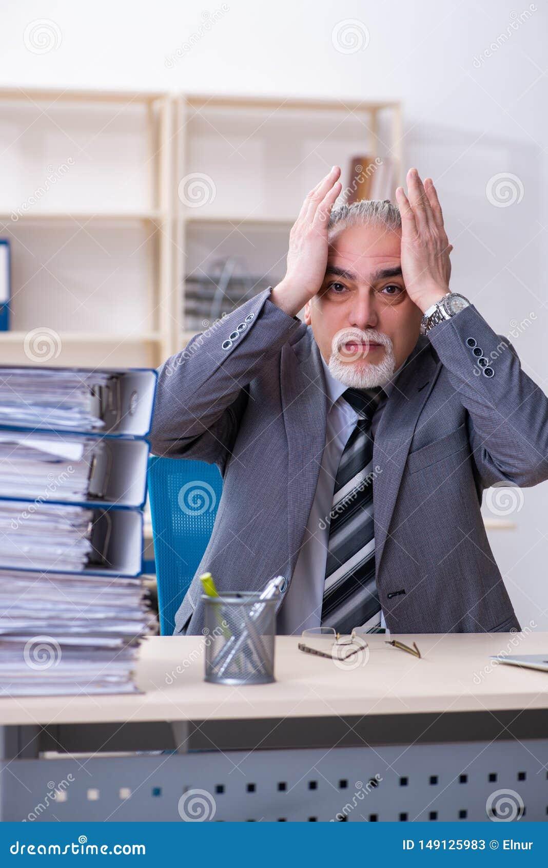 De oude mannelijke werknemer ongelukkig met het bovenmatige werk