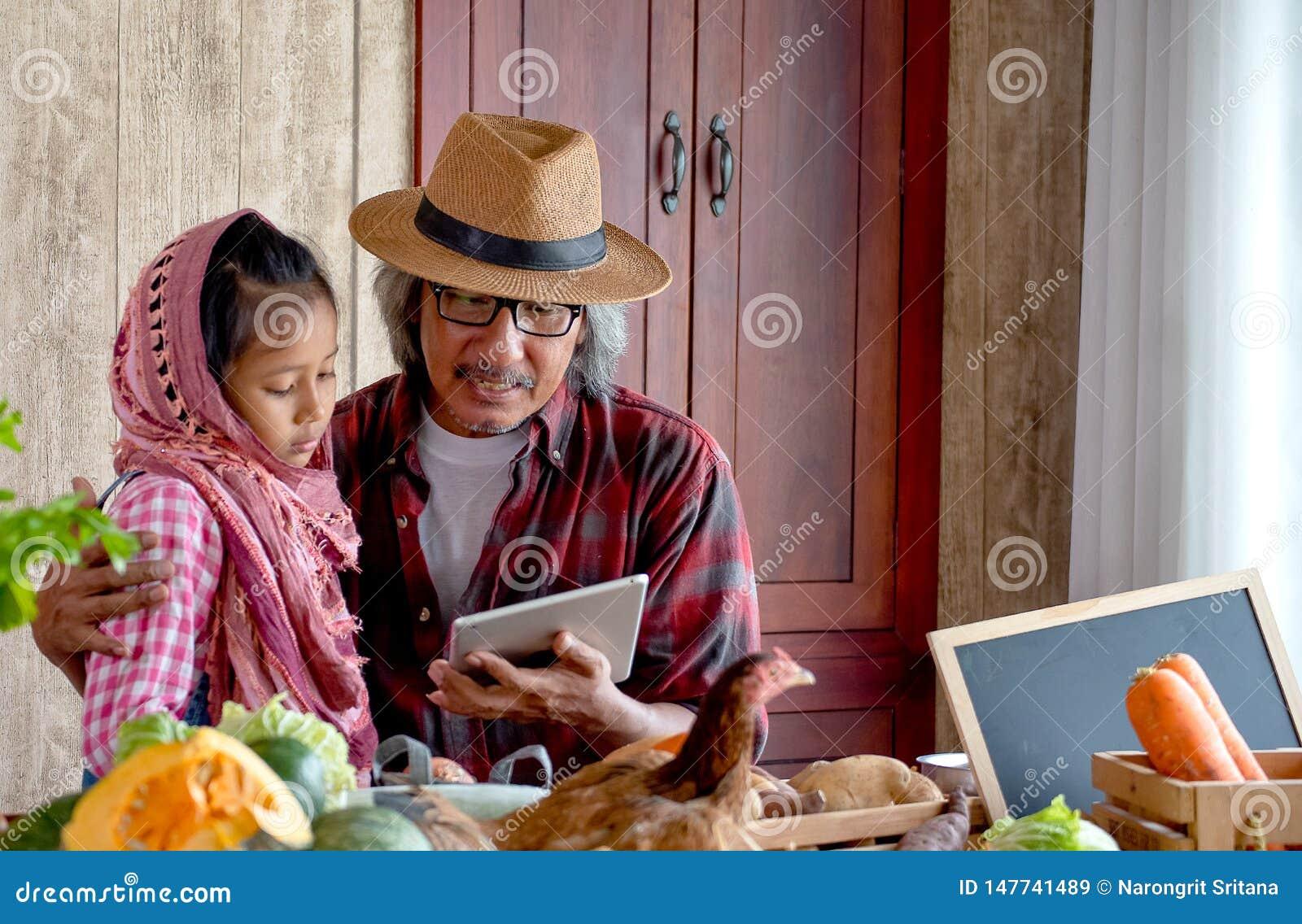 De oude mensengrootvader met hoed verklaart over zijn menu voor het koken aan zijn kleinkind door tablet in de keuken te gebruike