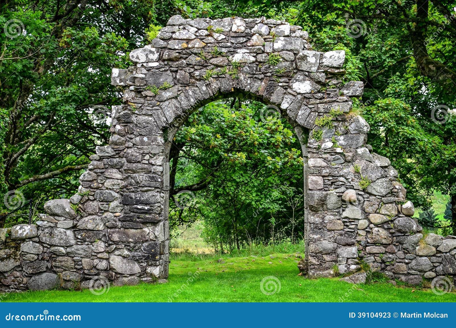 De oude muur van de steeningang in groene tuin