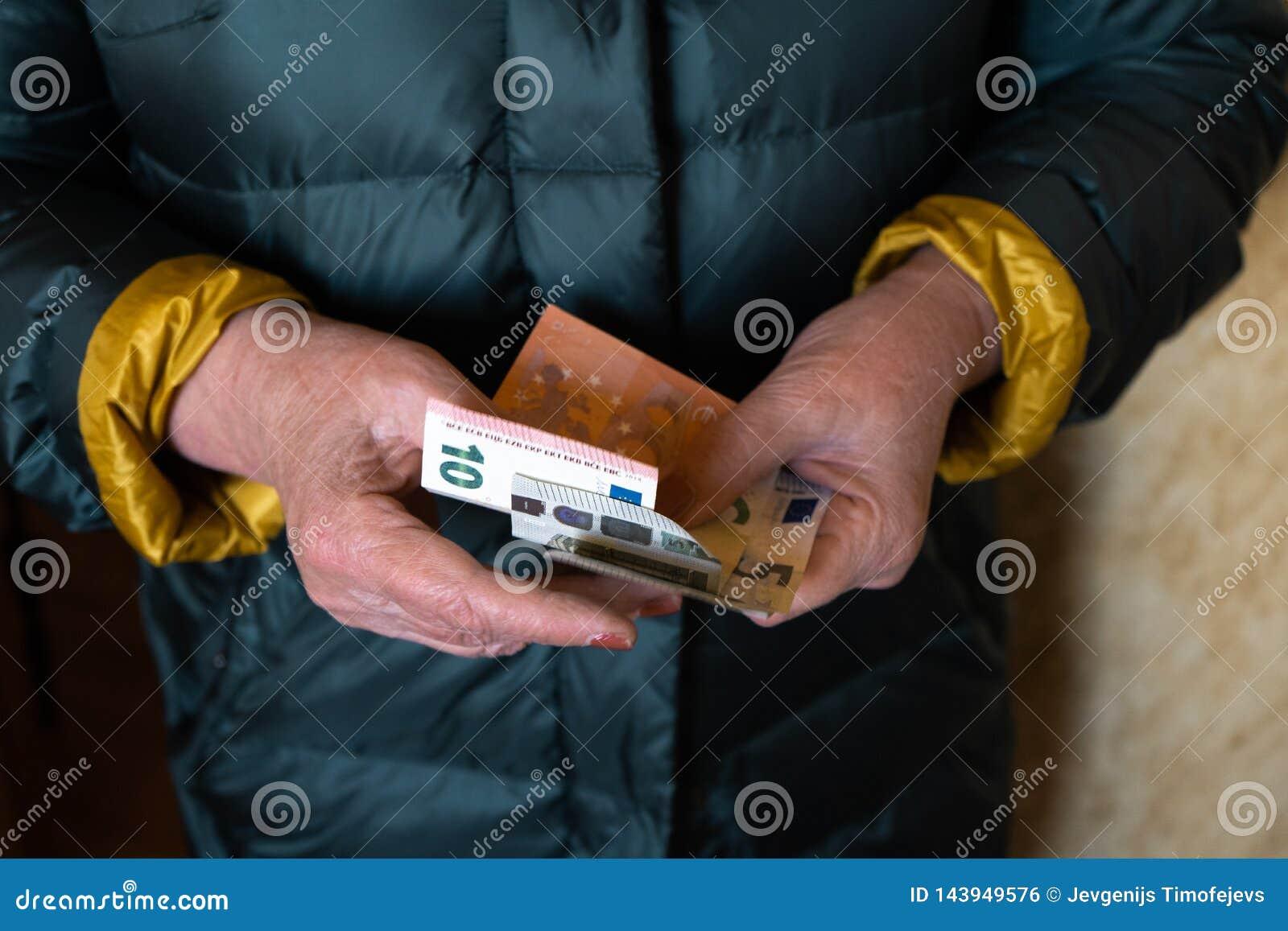 De oudere hogere vrouw houdt EURO bankbiljetten - Oosteuropees salarispensioen