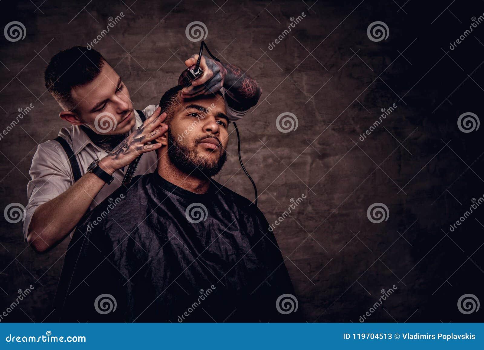 De ouderwetse professionele getatoeeerde kapper doet een kapsel aan een Afrikaanse Amerikaanse cliënt op donkere geweven
