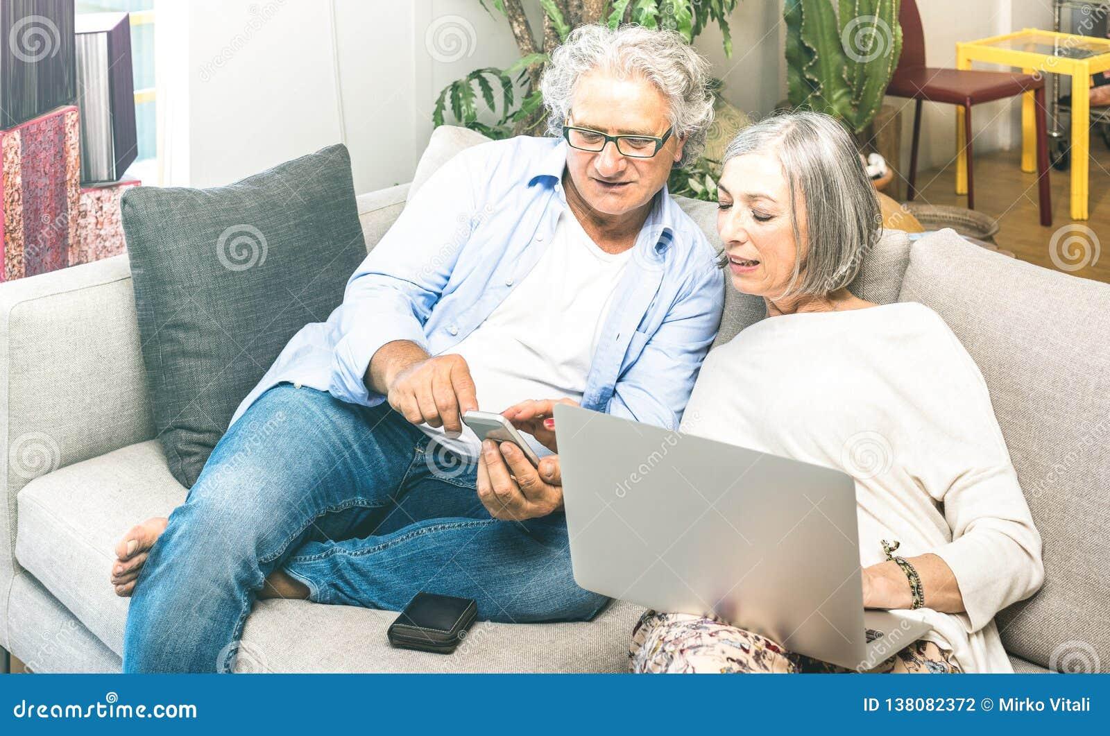 De oudste trok paar terug thuis gebruikend laptop computer op bank - Bejaarden en technologieconcept met rijpe mensen bij online