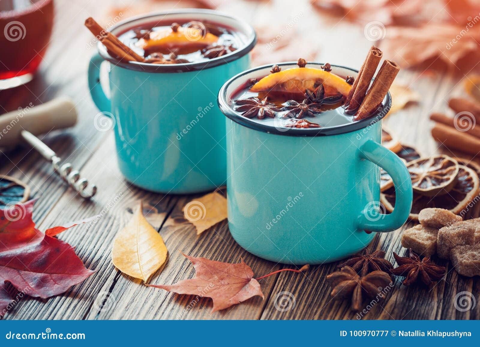 De overwogen wijn in blauwe geëmailleerde mokken met kruiden en citrusvruchten op lijst met de herfst gaat weg