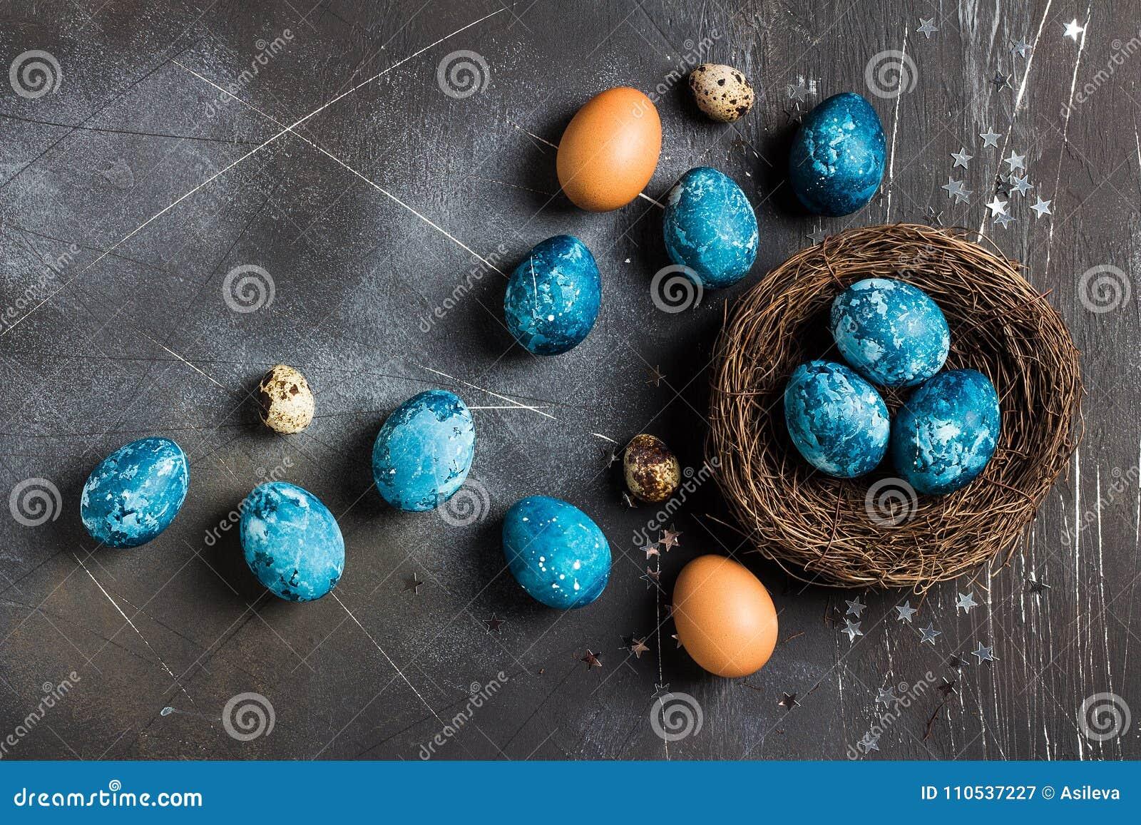 De paaseieren in langs geschilderd nest dienen blauwe kleur op donkere achtergrond in