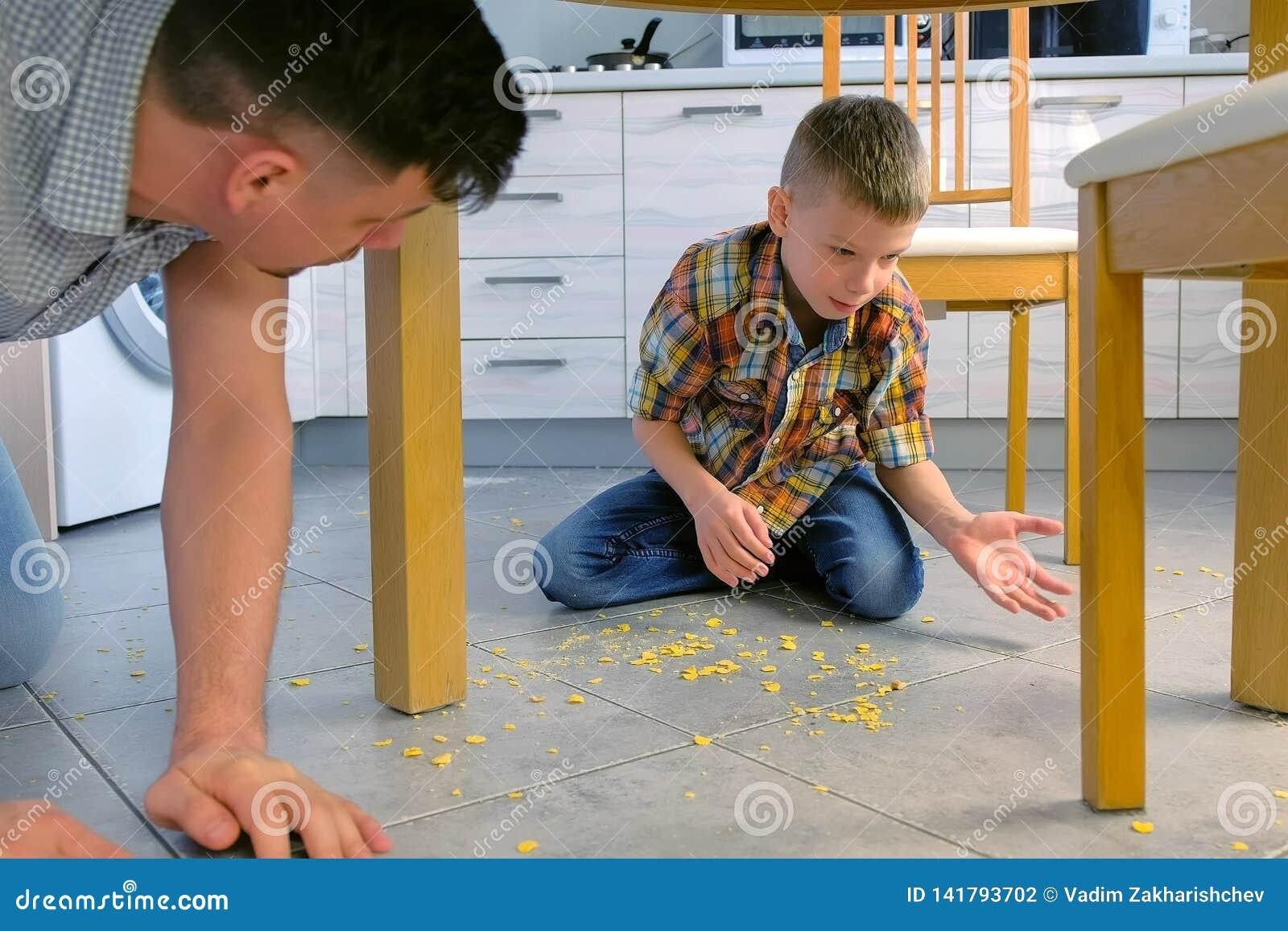 De papa berispt zijn zoon voor verspreid voedsel op de keukenvloer en maakt hem schoonmaken Maak cornflakes van de vloer schoon