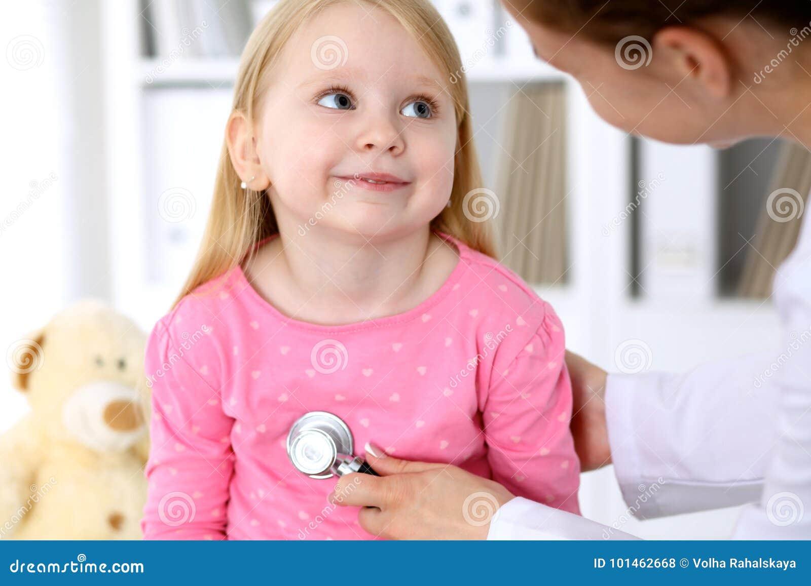 De pediater behandelt baby in het ziekenhuis Het meisje is onderzoekt door arts door stethoscoop Vertragingen en wapens