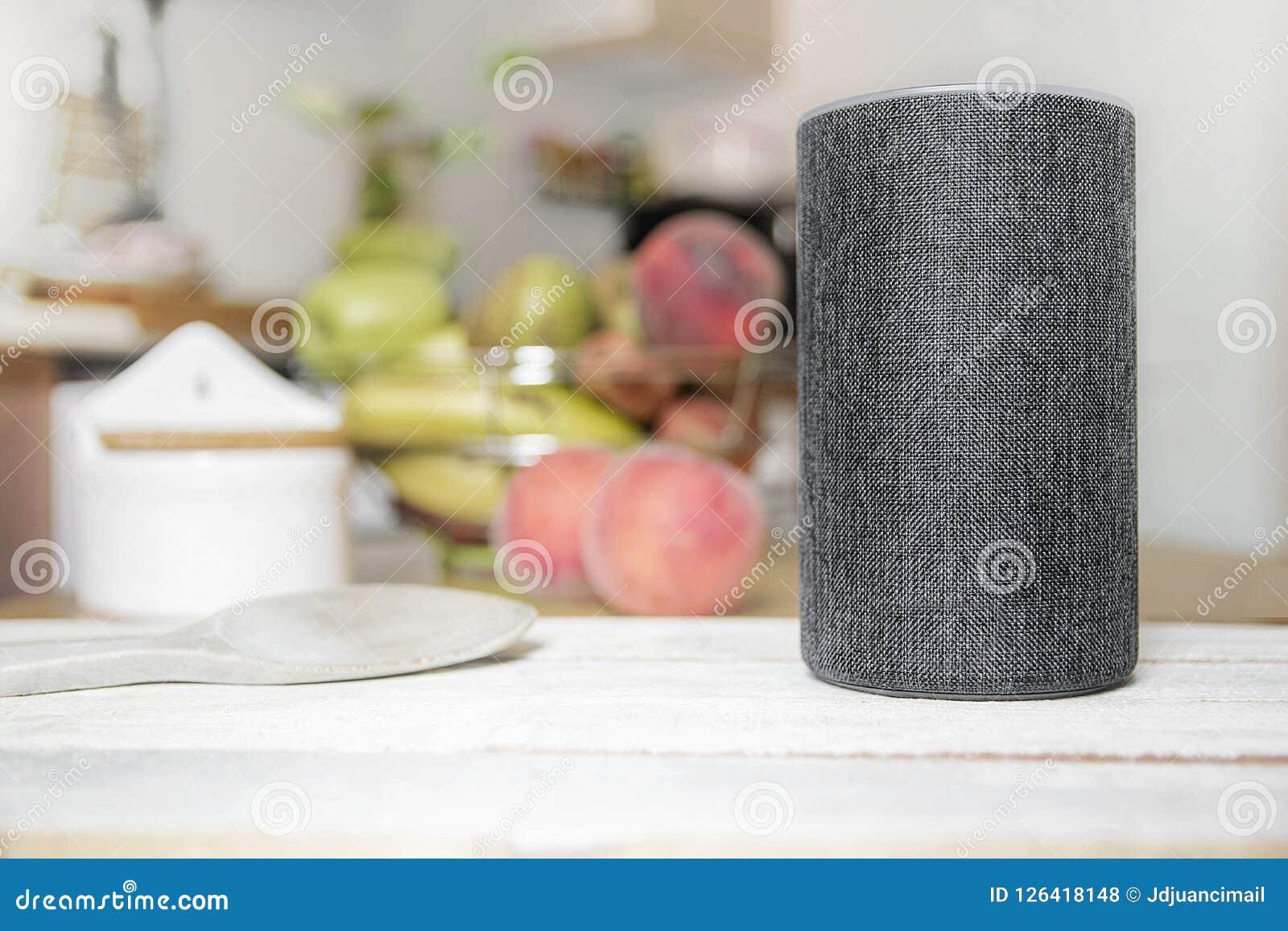 De persoonlijke medewerker sloot luidspreker op een houten lijst in een Slim Huis in een keuken aan Daarna, wat werktuigen, voeds