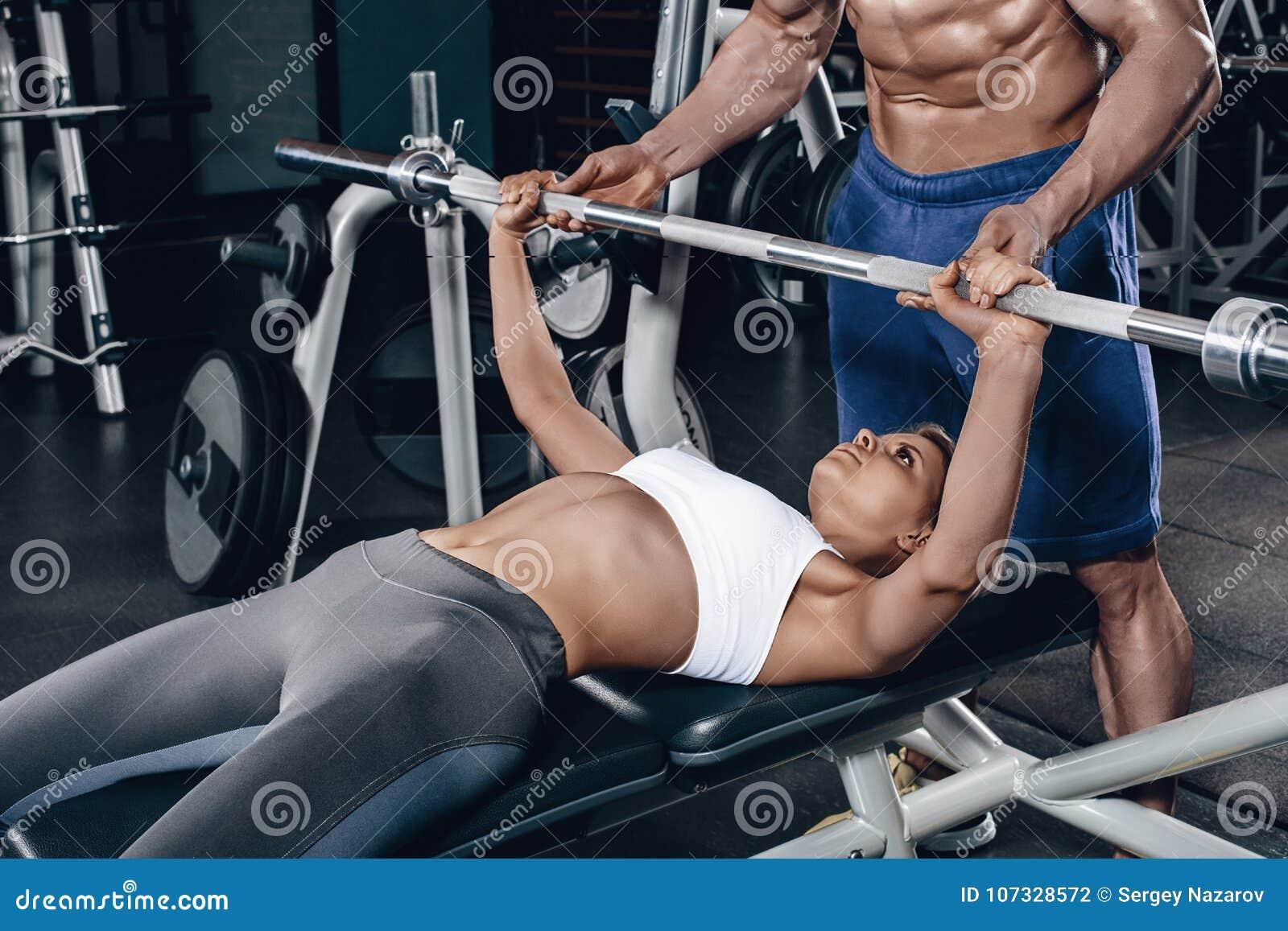 De persoonlijke trainer die een jonge vrouw helpen heft een barbell op terwijl het uitwerken in een gymnastiek