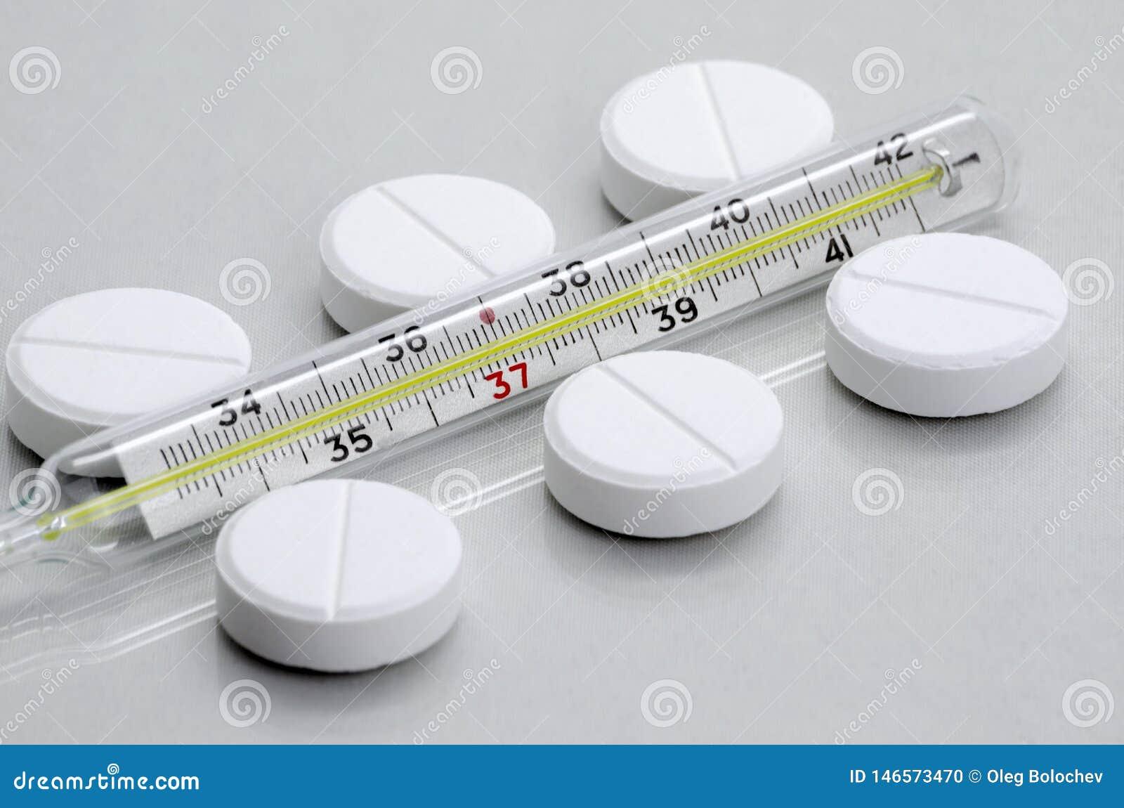 De pillen liggen naast de medische thermometer