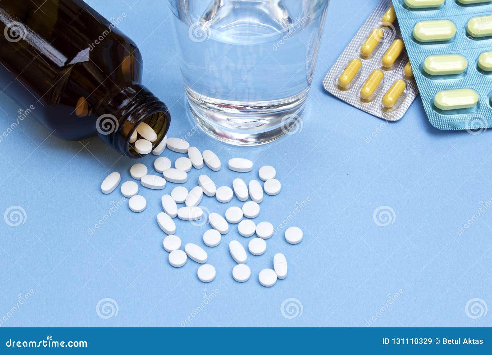 De pillen morsten uit pillenfles, geneeskrachtig tabletten en water op blauwe achtergrond