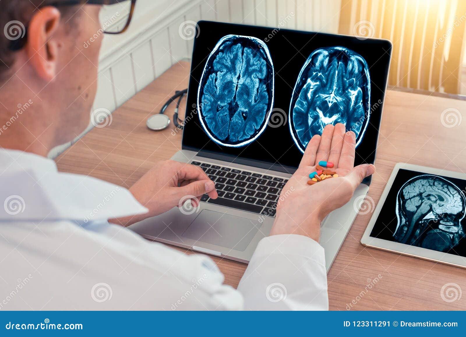 De pillen van de artsenholding voor ziekte met röntgenstraal van hersenen en schedel op laptop Digitale tablet op het houten bure