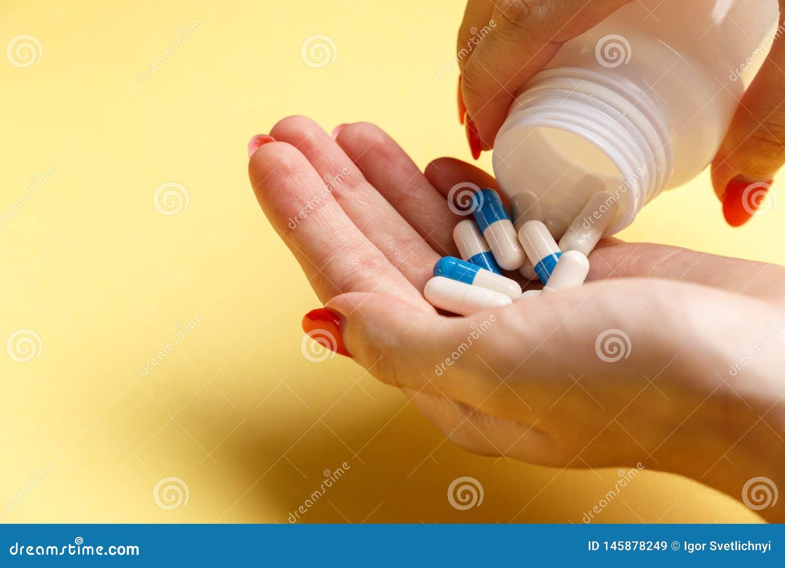 De pillen van de vrouwenholding op hand