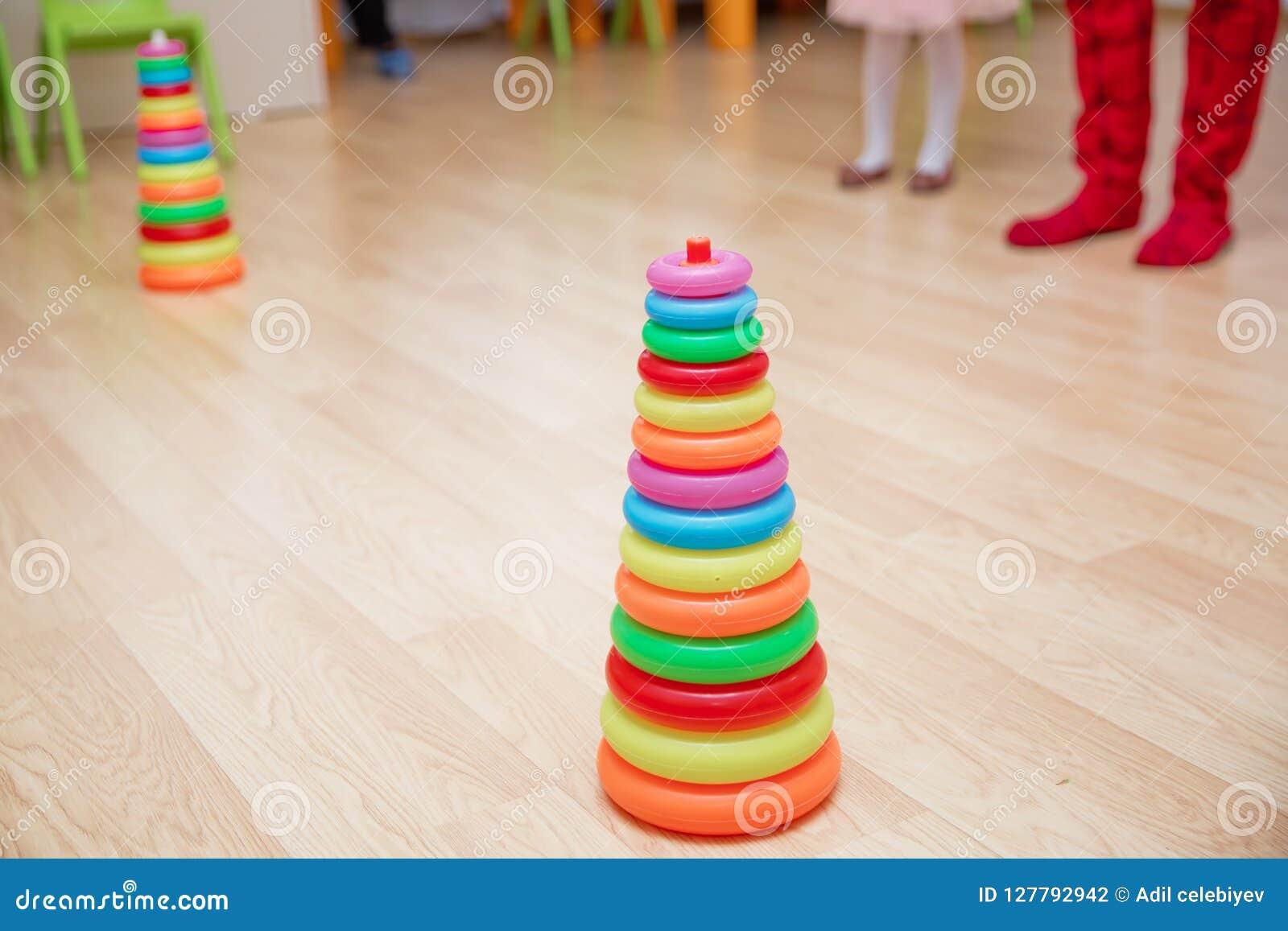 De piramide bouwt van gekleurde houten ringen met een clownhoofd op bovenkant Stuk speelgoed voor babys en peuters vreugdevol om
