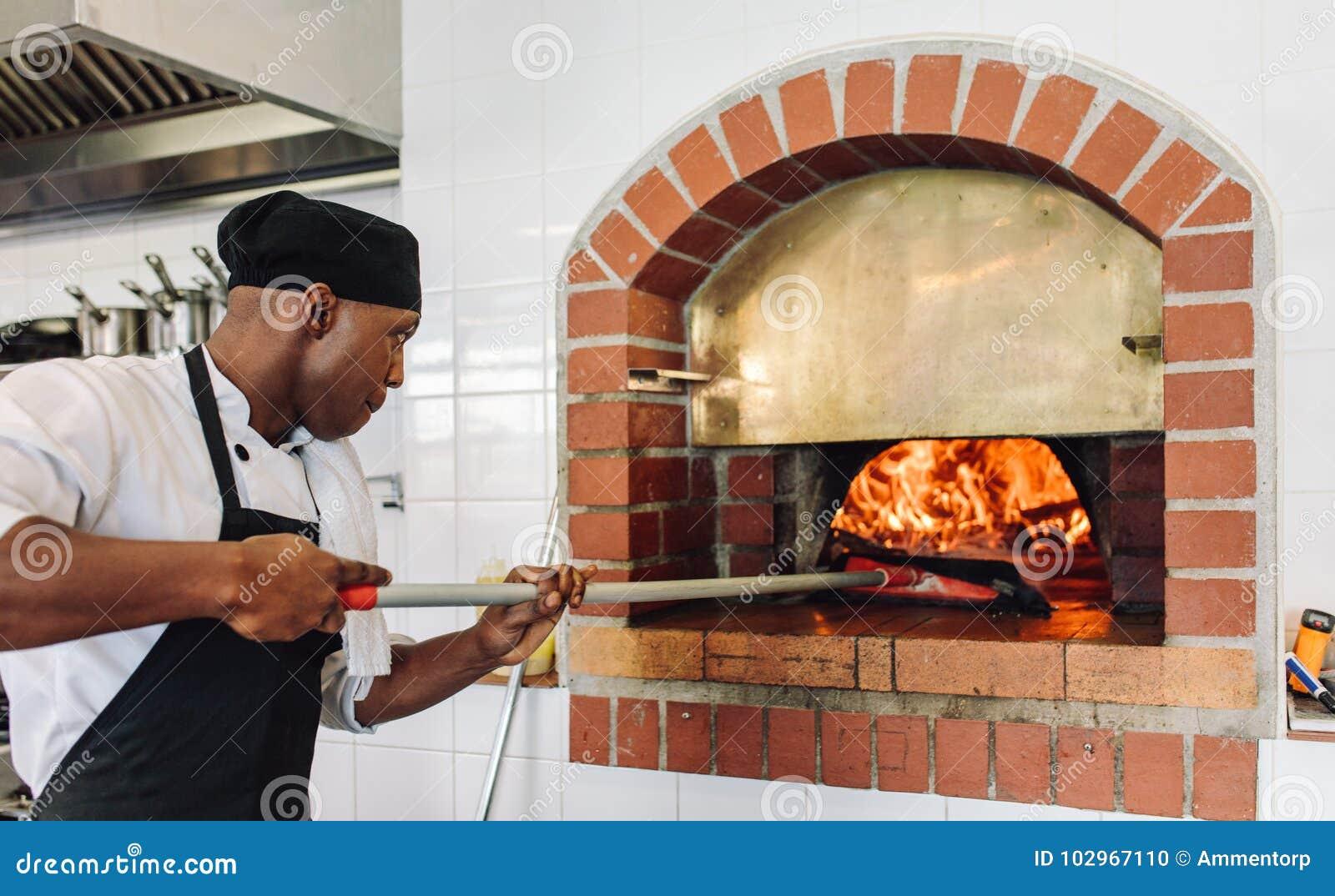 De pizza van het chef-kokbaksel in hout in brand gestoken oven