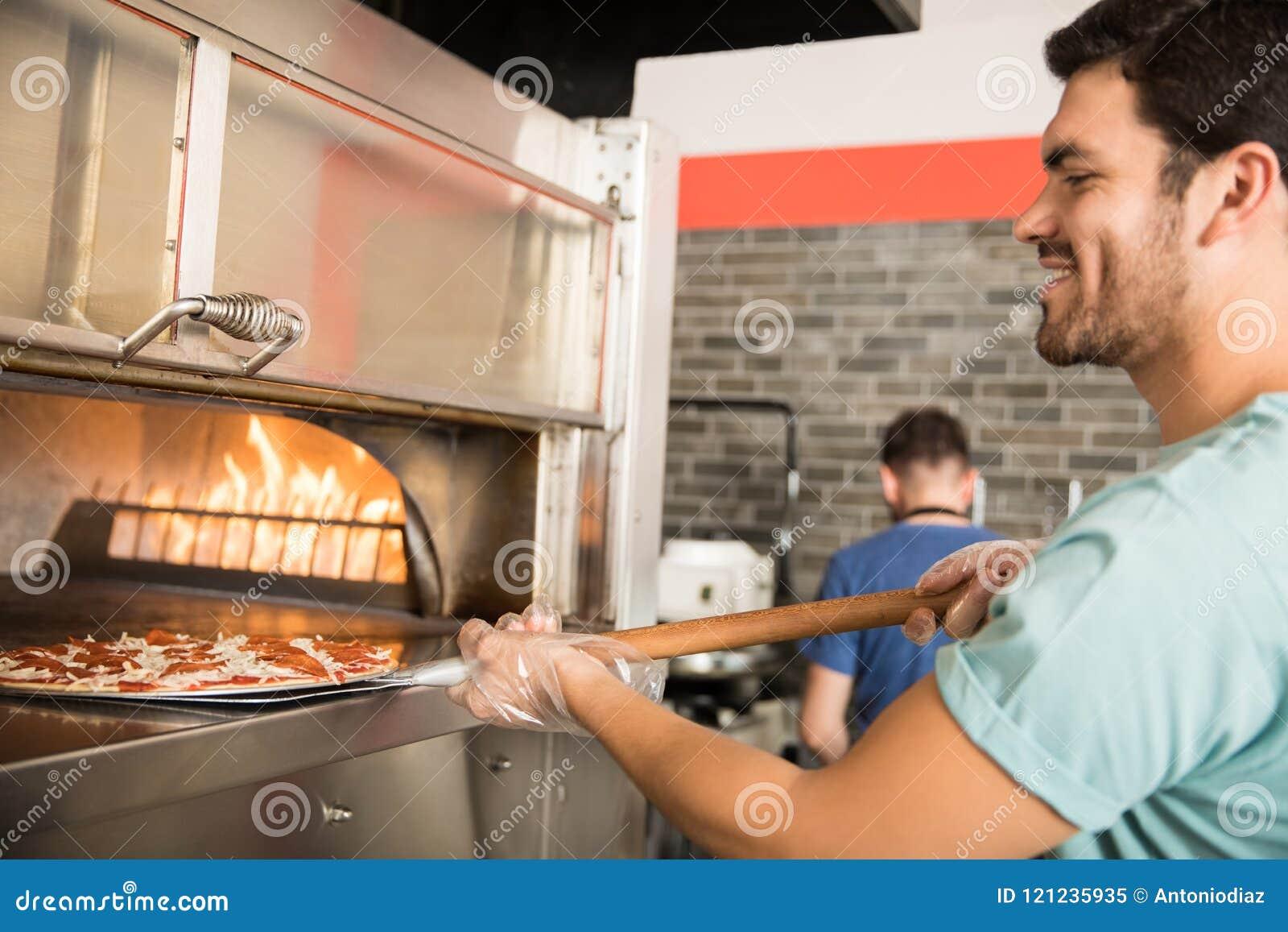 De pizzabrood van het chef-kokbaksel in oven bij commerciële keuken
