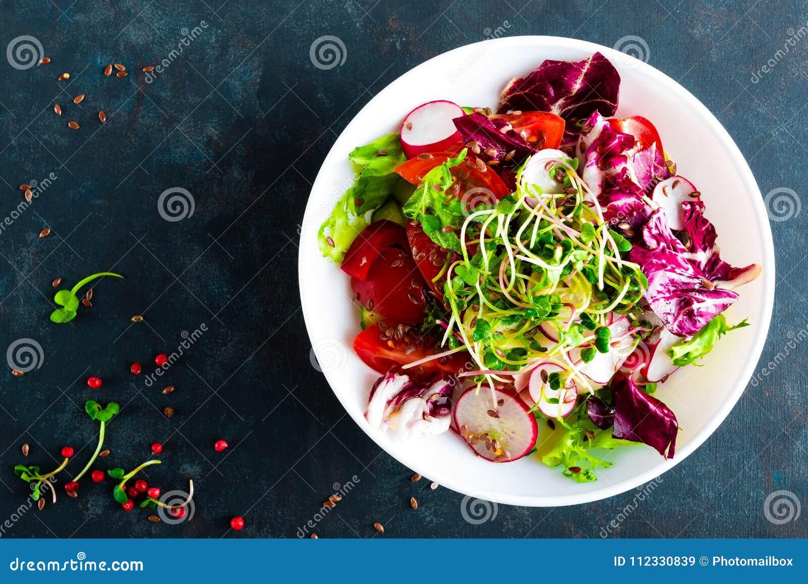 De plaat van de verse groentesalade van tomaten, Italiaanse mengeling, peper, radijs, groen spruiten en lijnzaad Vegetarische sch