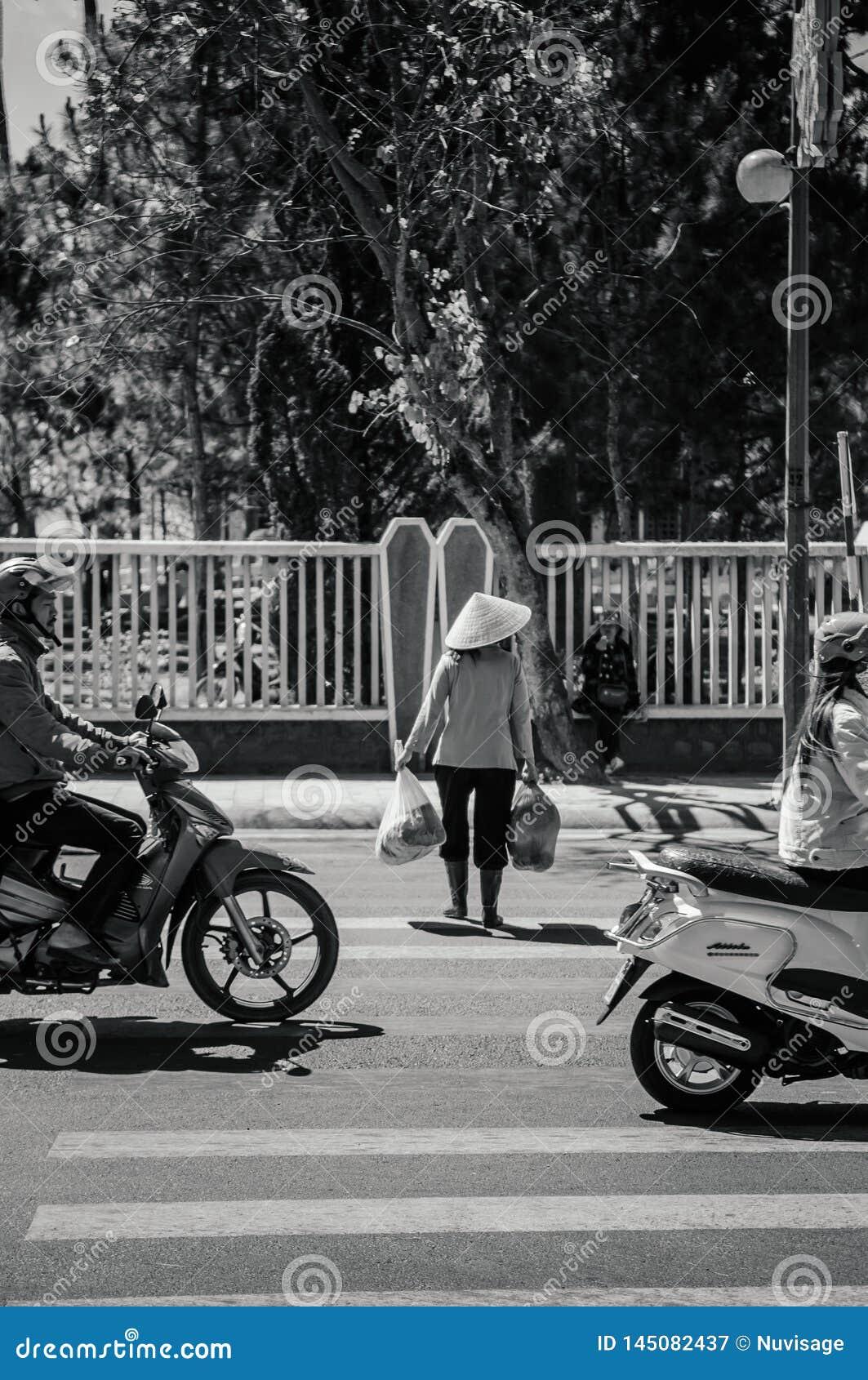 De plaatselijke bevolking draagt Vietnamese hoed kruisend straat met verkeer in DA Lat - Vietnam