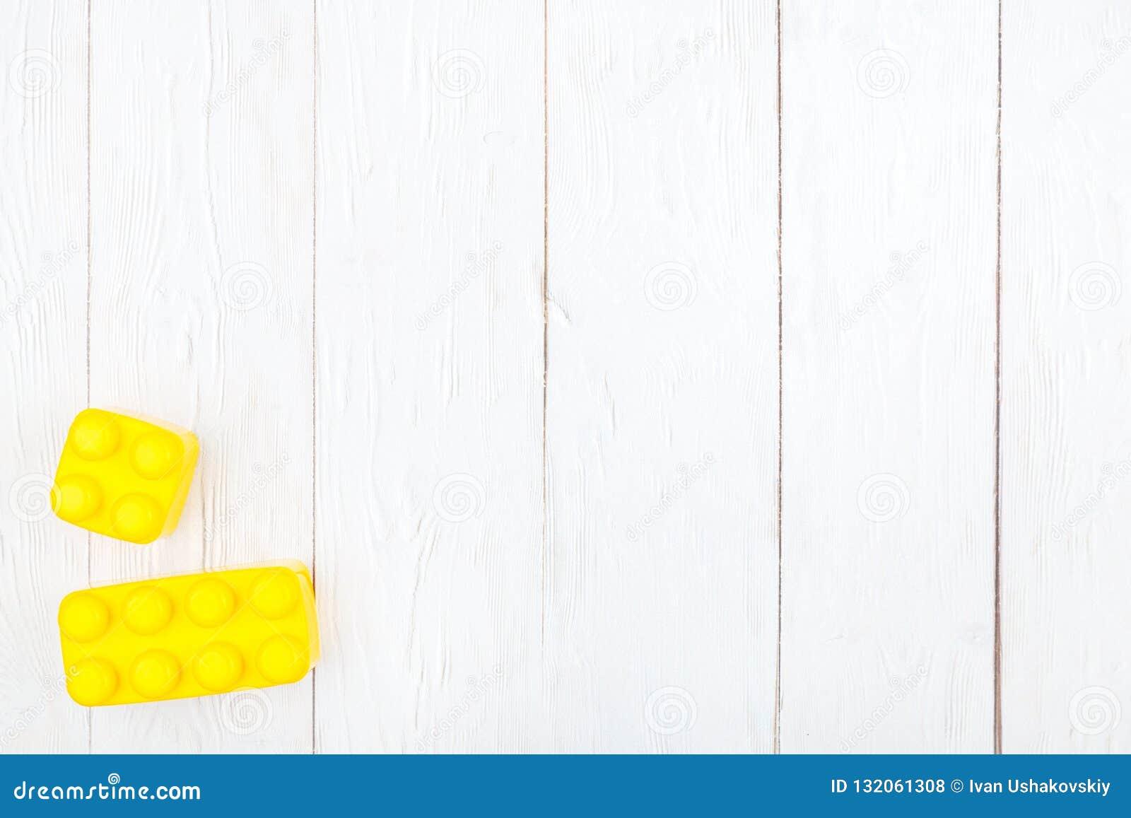 De plastic bouwstenen van kinderen Vlak leg op houten backgroun