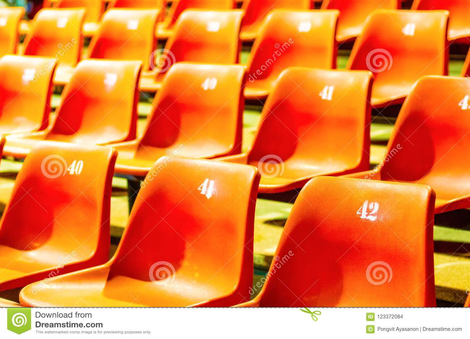De plastic sinaasappel van de rijstoel met alle aantallen in grote conferentie ro