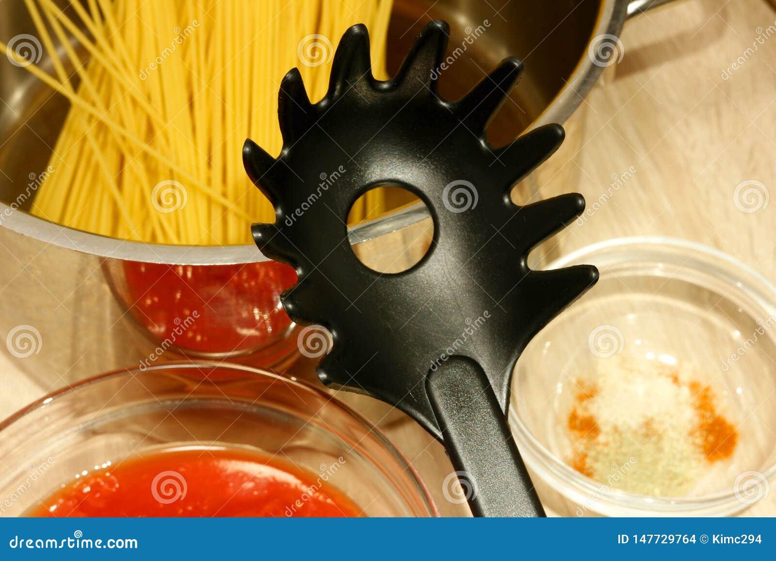 De plastic spaghettiserver ligt op de rand van een metaaldiesteelpan met ongekookt spaghettistro wordt gevuld