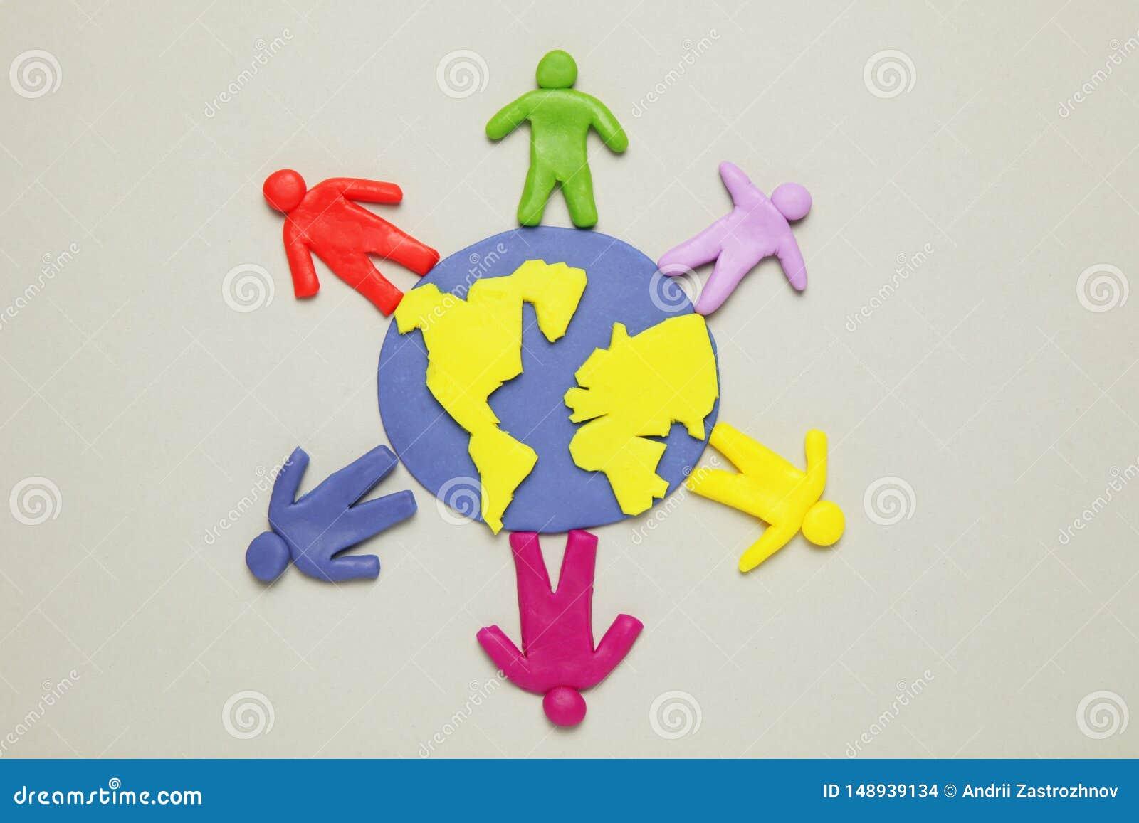 De plasticinebeeldjes van mensen van verschillende rassen zijn op aarde Een verscheidenheid van interactie, mededeling en globali