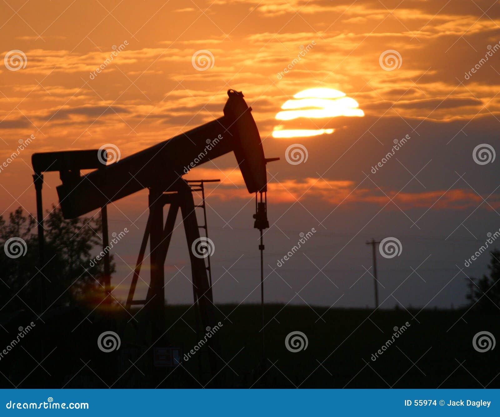 De pomphefboom van de olie bij zonsondergang
