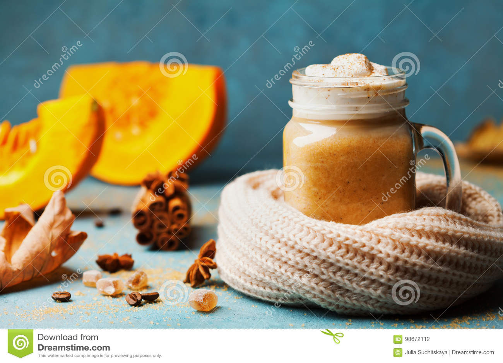 De pompoen kruidde latte of de koffie in glas verfraaide gebreide sjaal op turkooise uitstekende achtergrond De herfst, dalings o