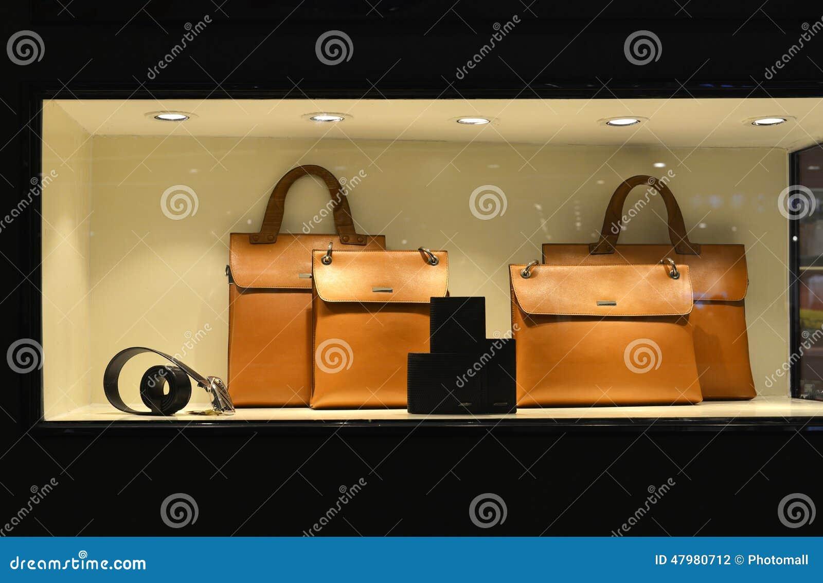 De Portefeuille van de de handtasriem van het luxeleer in winkelvenster door geleide lichten omhoog wordt aangestoken dat