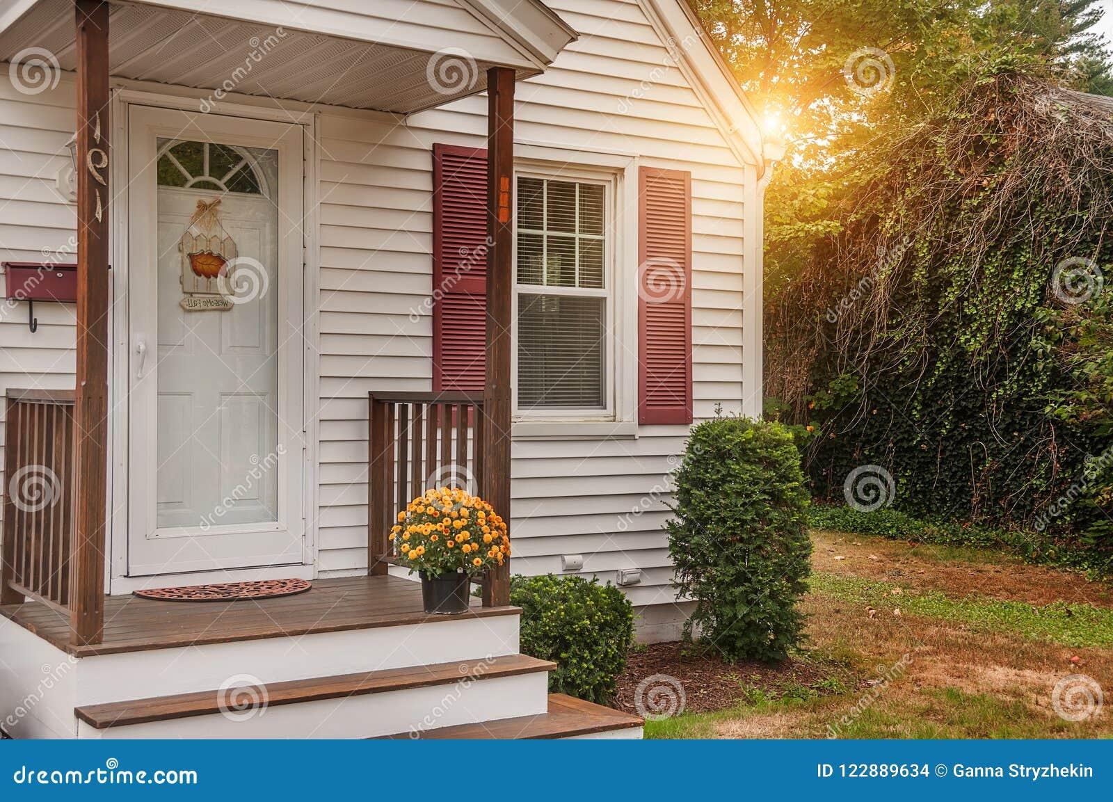 De portiek van een klein comfortabel blokhuis en met gele chrysanten op de drempel De V.S. maine Huis eenvoudig comfort