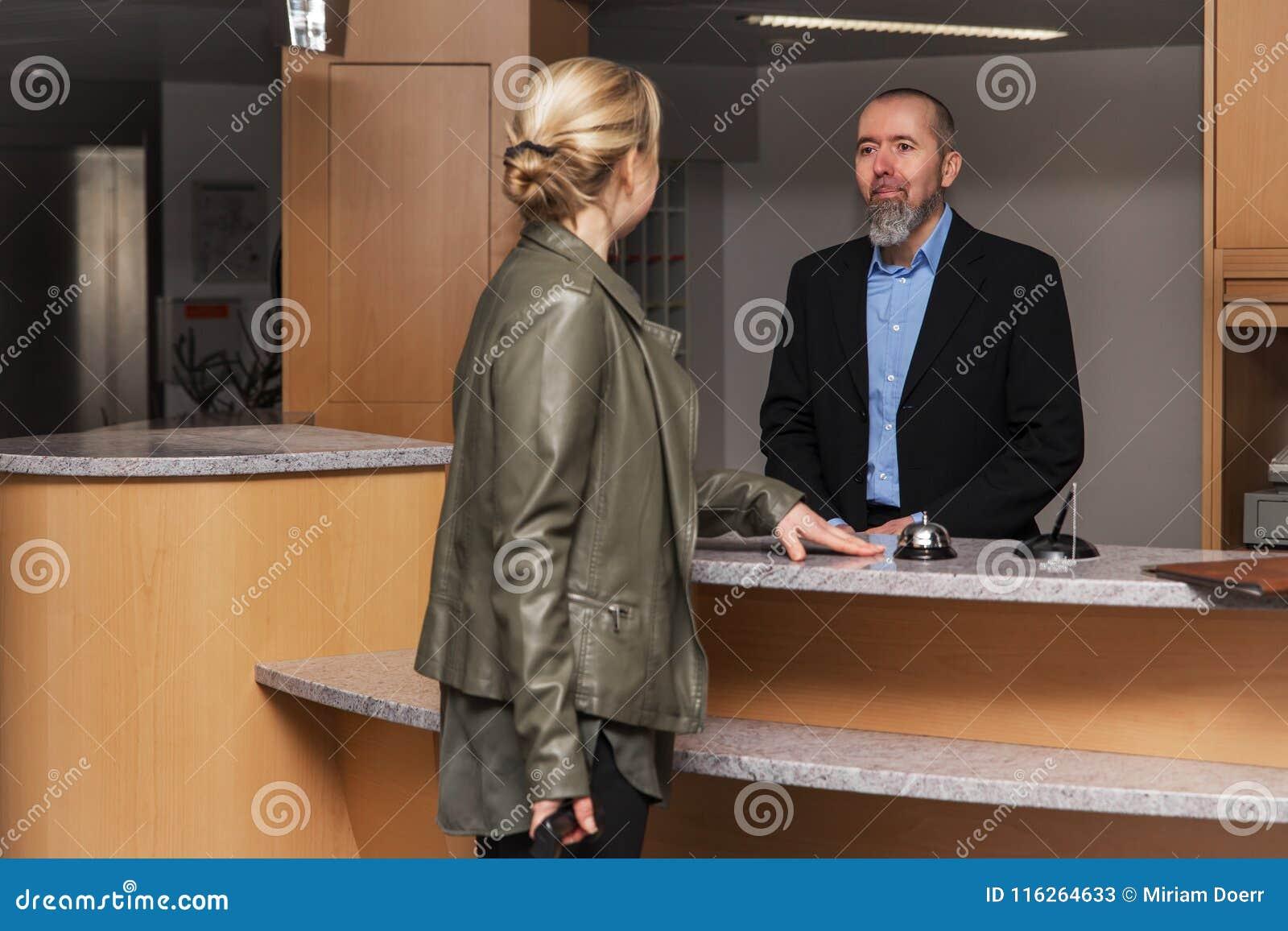 De portier in een hotel smilling aan een vrouwelijke gast