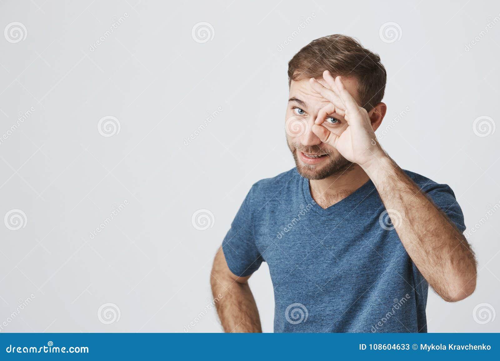 De positieve gebaarde kerel in blauwe t-shirt toont o.k. teken, aantoont dat alles, akkoord gaat fijn is Zekere vrolijke mens