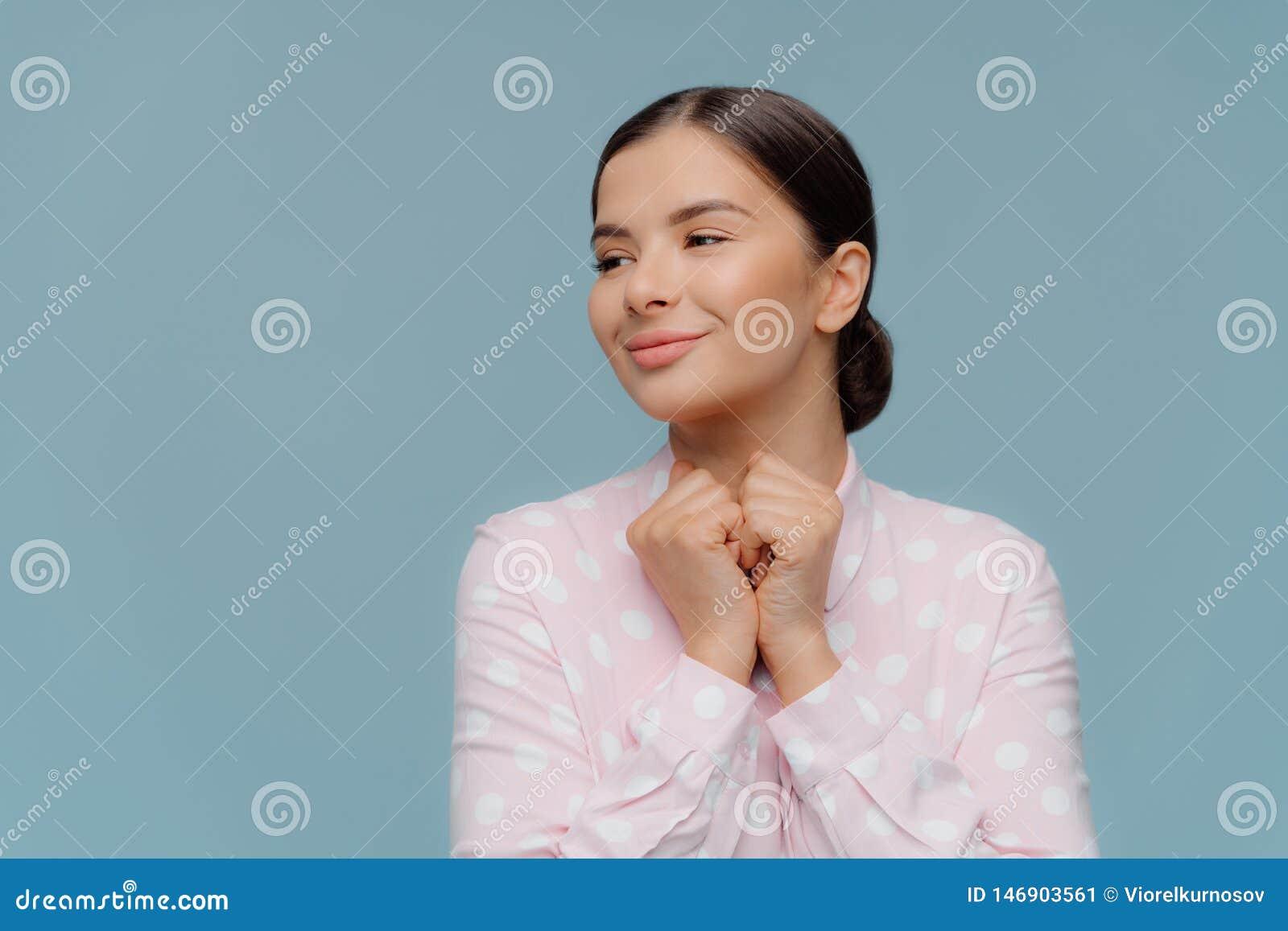 De positieve optimistische die dame houdt vuisten onder kin worden samengeperst, kijkt gladfully opzij, draagt stipoverhemd, kijk