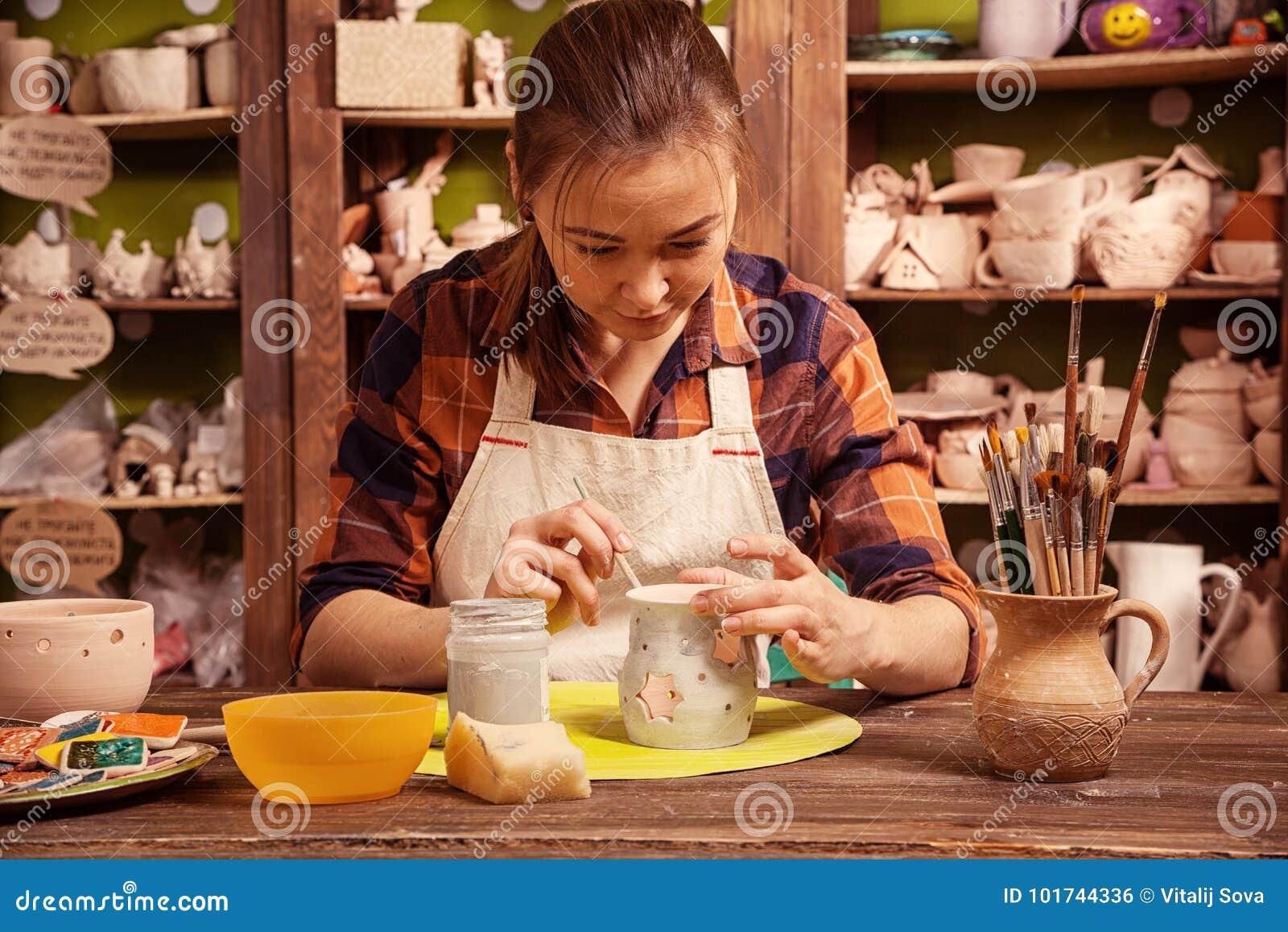 De pottenbakker schildert een klei