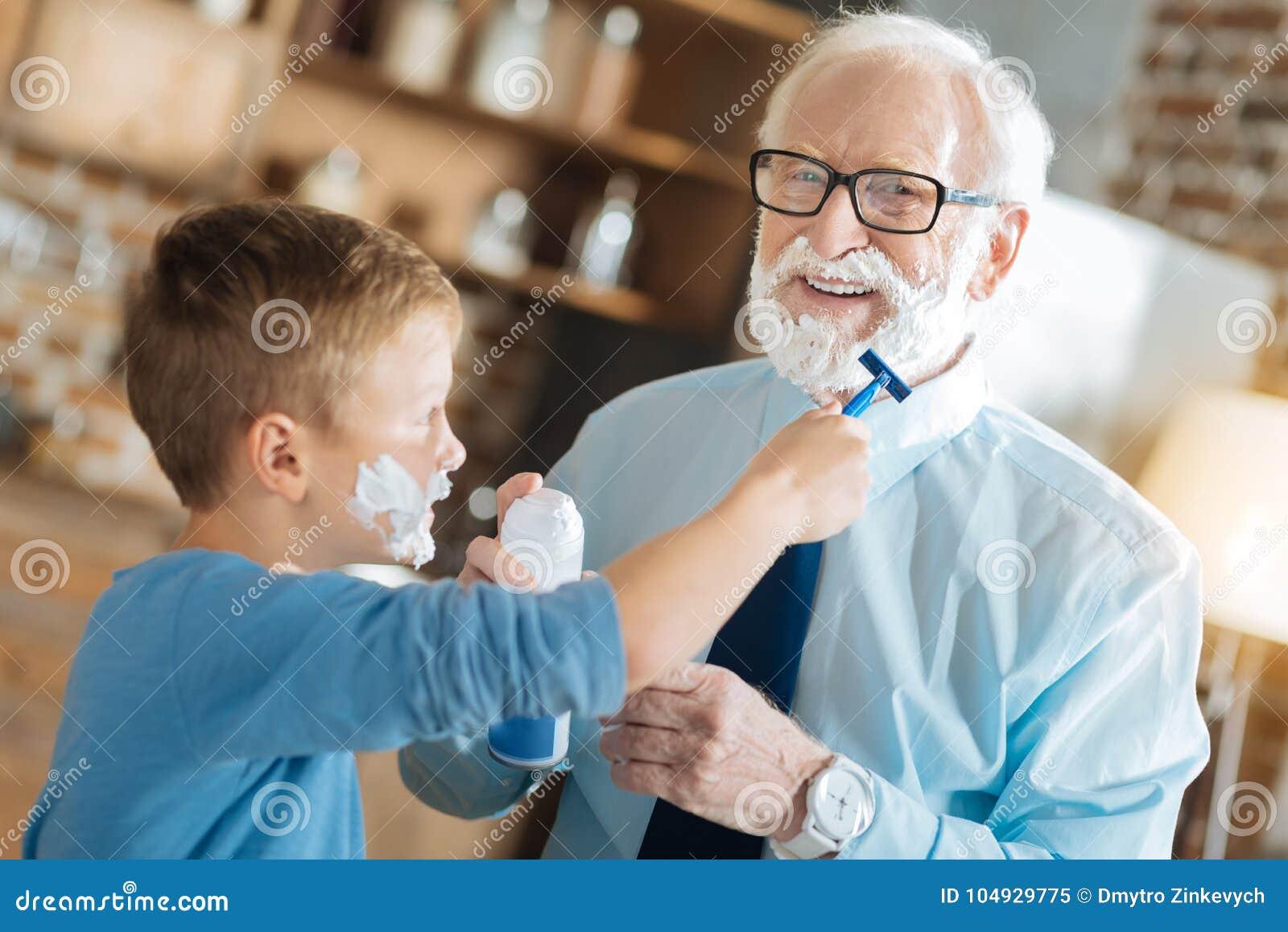 De prettige jongen die van nice zijn grootvader scheren stock afbeelding afbeelding 104929775 - Turquoise ruimte van de jongen ...