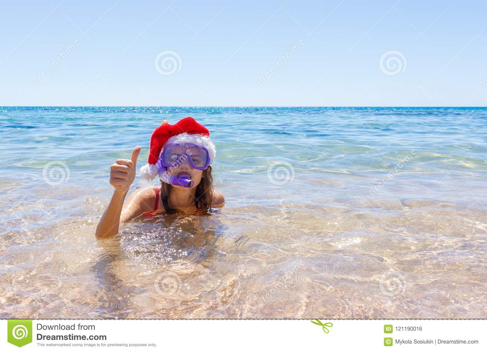 De pretvrouw die van de strandvakantie een maskerbuis en een Kerstmishoed voor het zwemmen in oceaanwater dragen Close-upportret