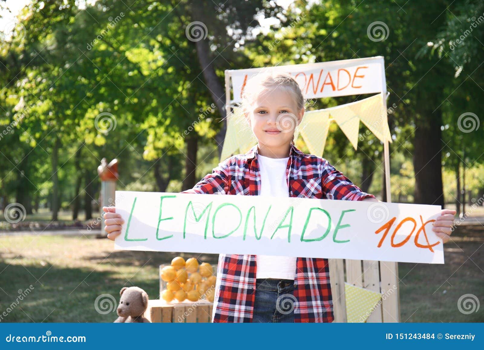 De prijsbanner van de meisjeholding dichtbij limonadetribune in park