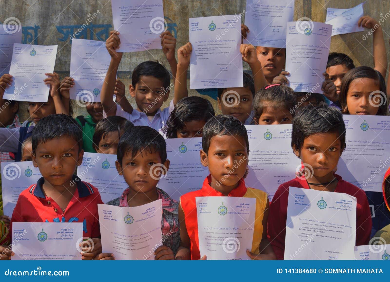 De primaire studenten toont hun groetenbrieven die door de Belangrijkste minister van West-Bengalen naar hen werden verzonden
