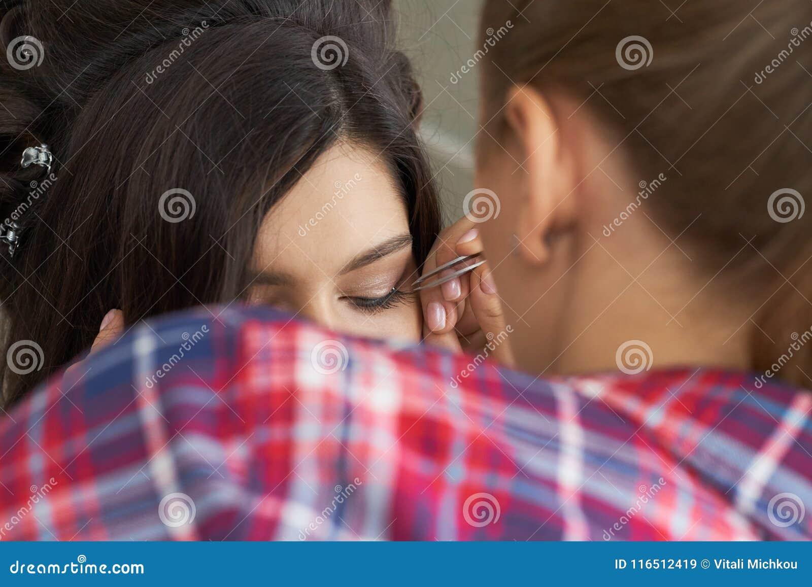 De procedure dichte omhooggaand van de wimperverwijdering Mooie Vrouw met lange zwepen in een schoonheidssalon Wimperuitbreiding