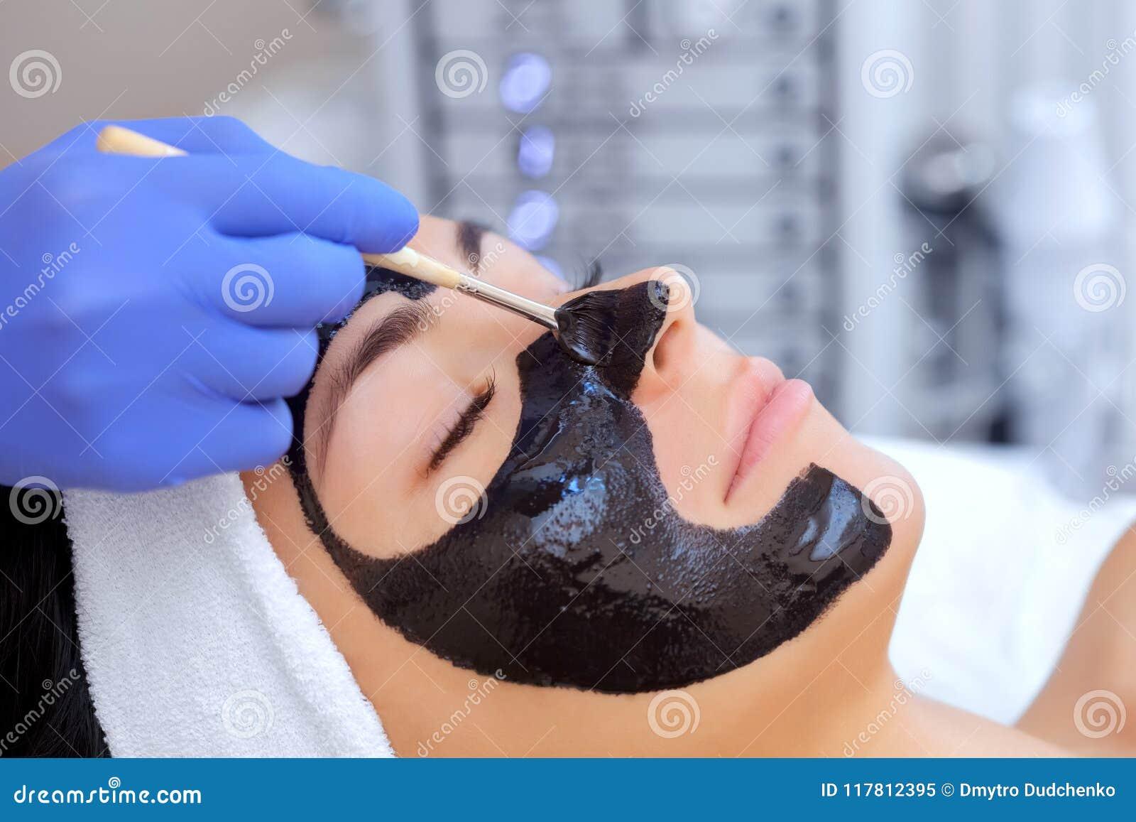 De procedure om een zwart masker op het gezicht van een mooie vrouw toe te passen