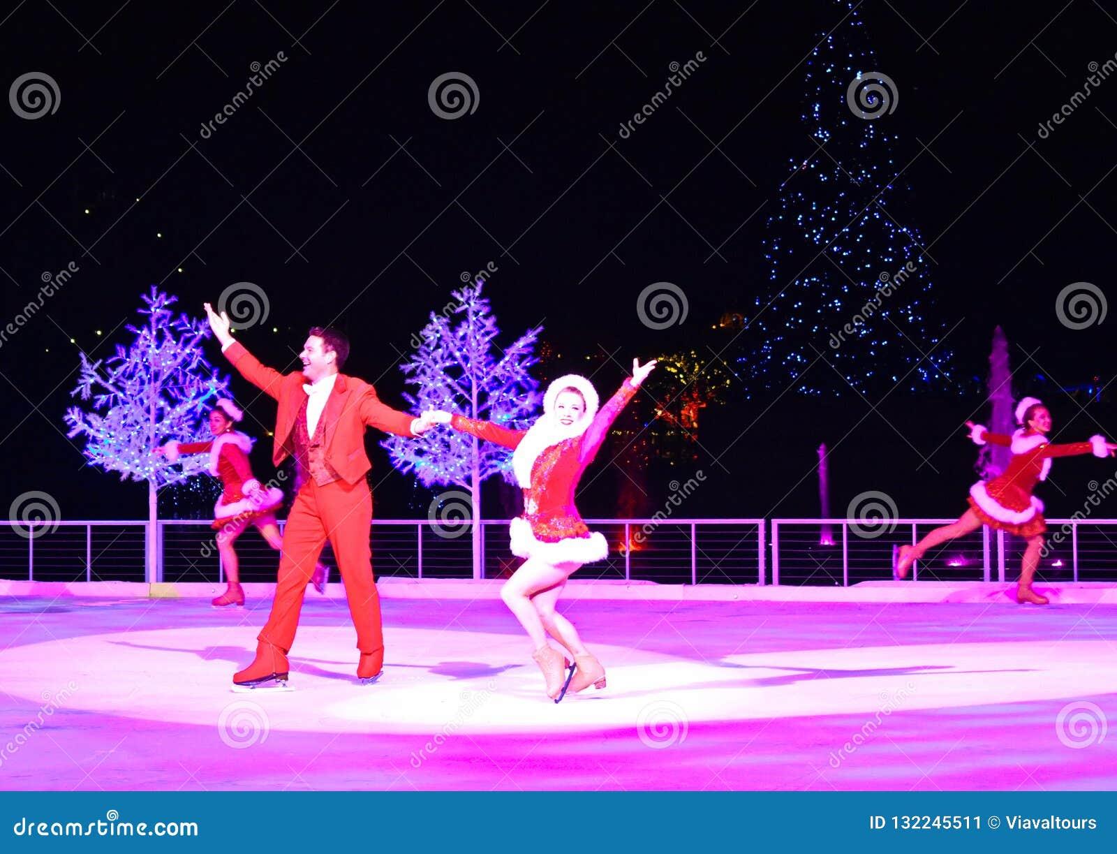 De professionele man en vrouwencijferschaatsers die bij Kerstmis op ijs presteren tonen op Internationaal Aandrijvingsgebied