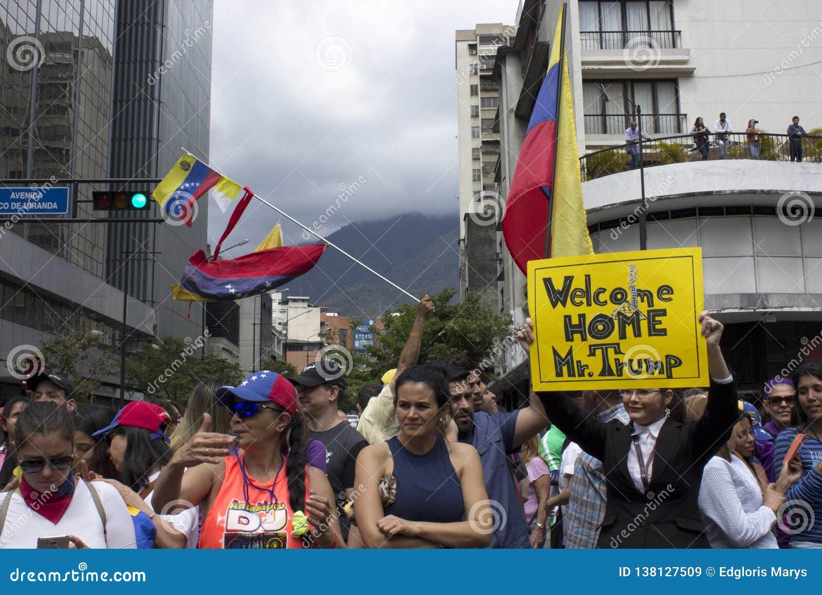 De protesteerders houden banners instemmend met de agressieve bewegingen van Donald Trump op Venezuela