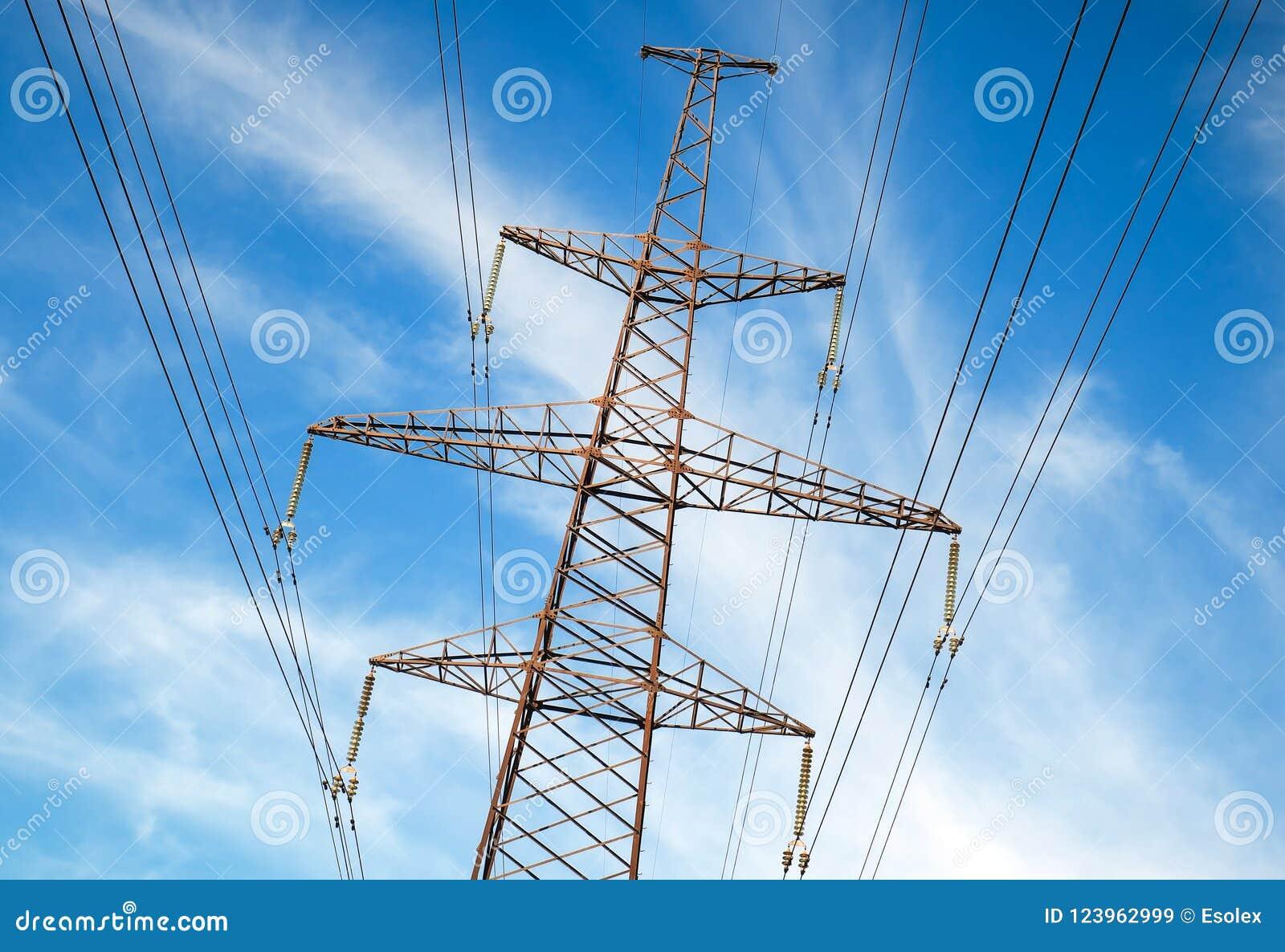 De pylonen van een hoogspanningsmacht tegen bewolkte hemel