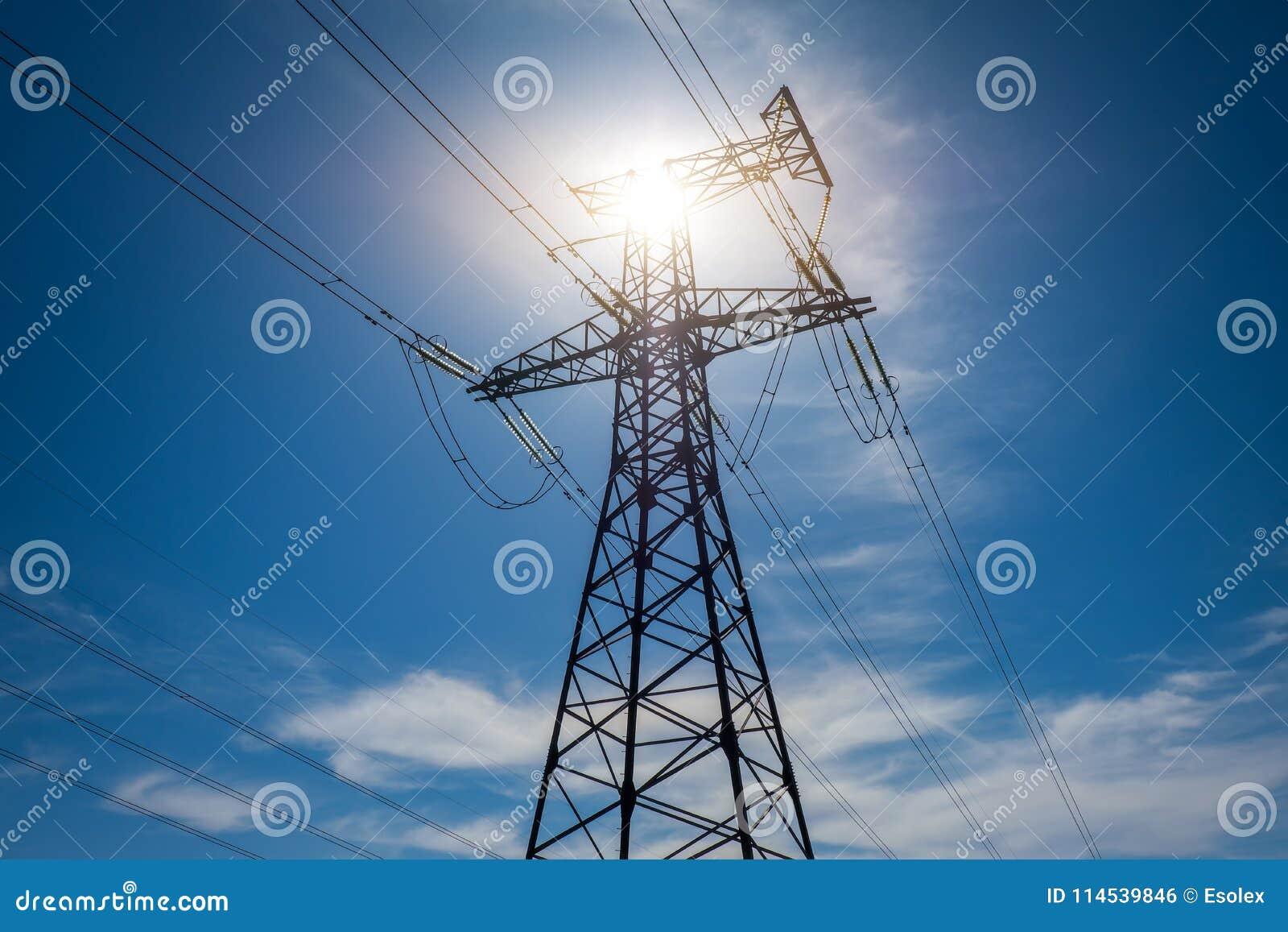 De pylonen van een hoogspanningsmacht tegen blauwe hemel