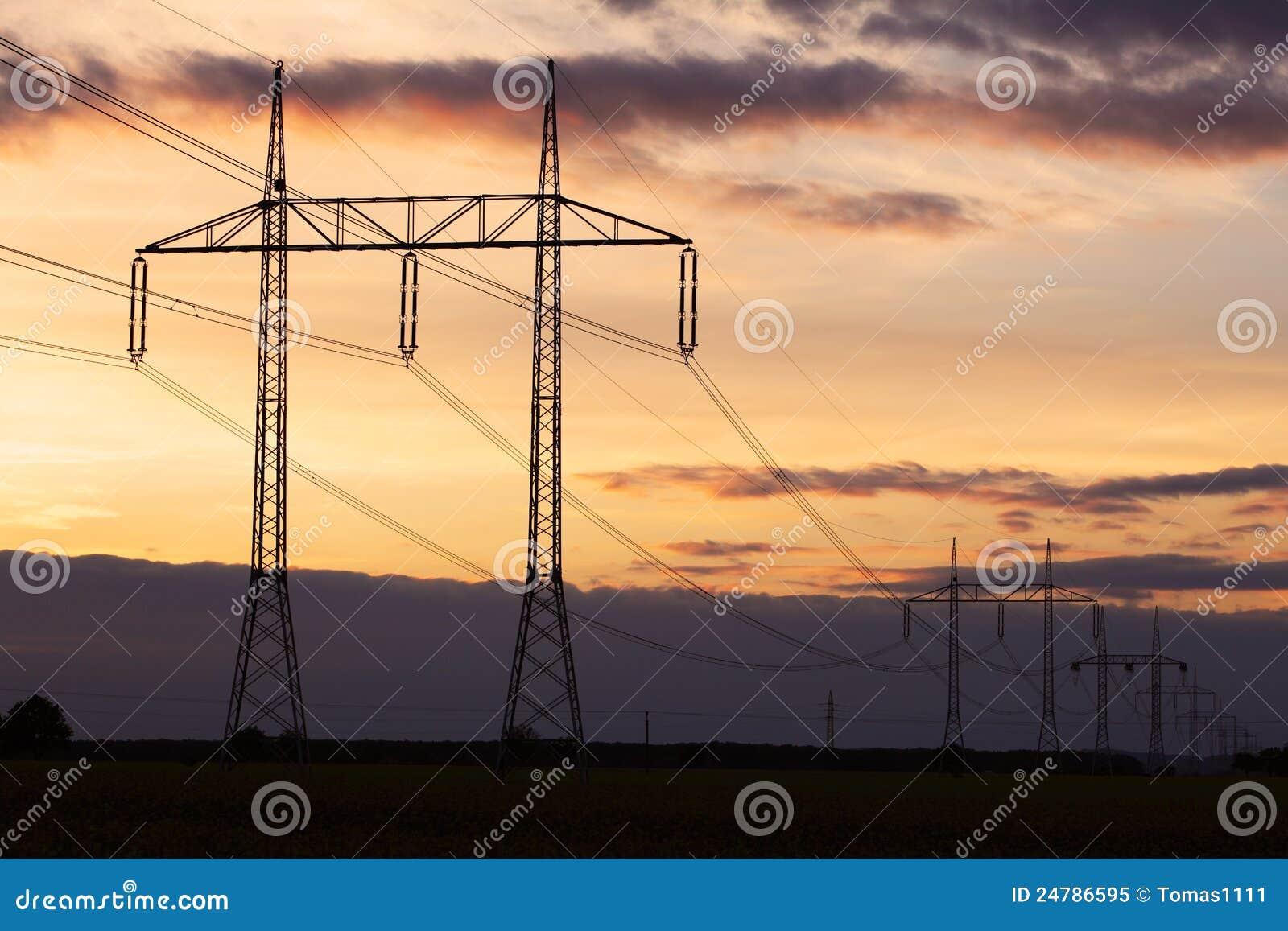 De pyloon van de elektriciteit op zonsondergang