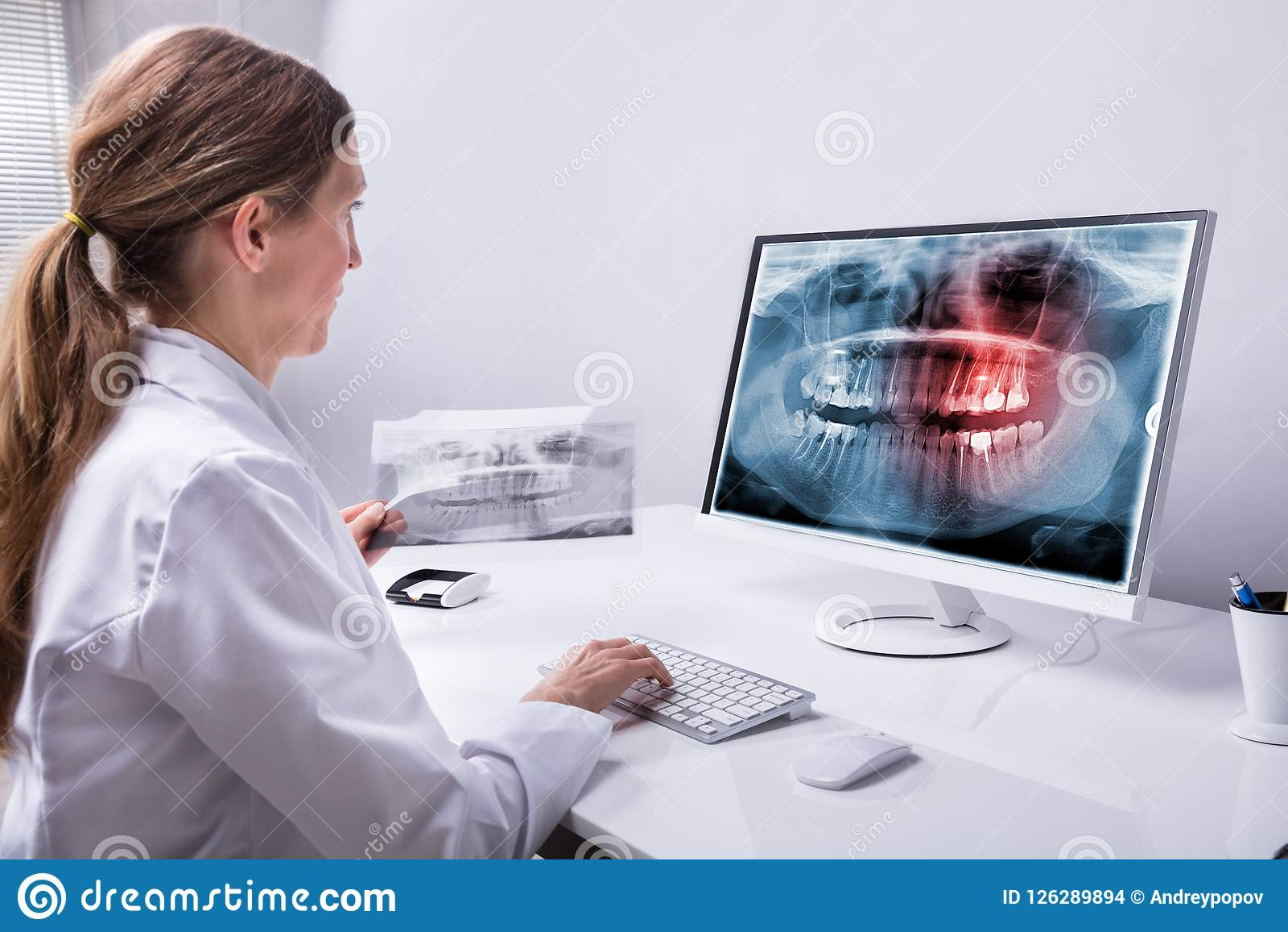 De Röntgenstraal van tandartslooking at teeth op Computer