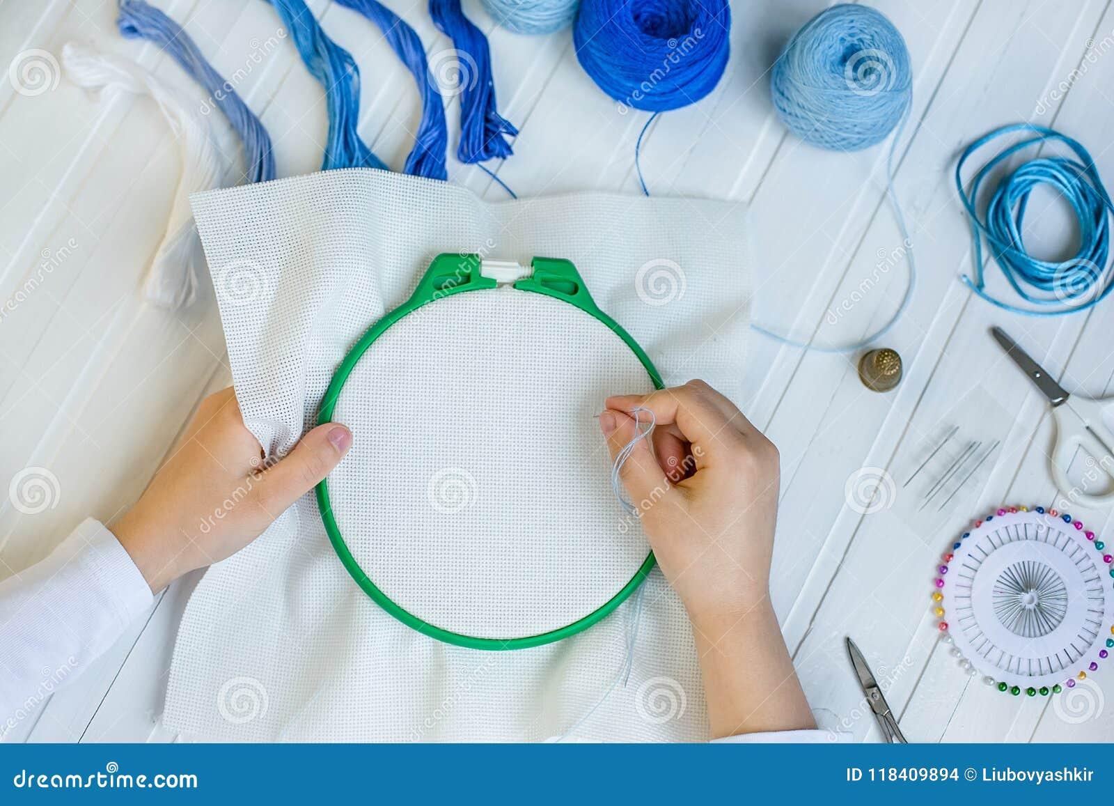 De reeks voor borduurwerk, borduurwerkhoepel, linnenstof, draad, schaar, borduurde naaldbed