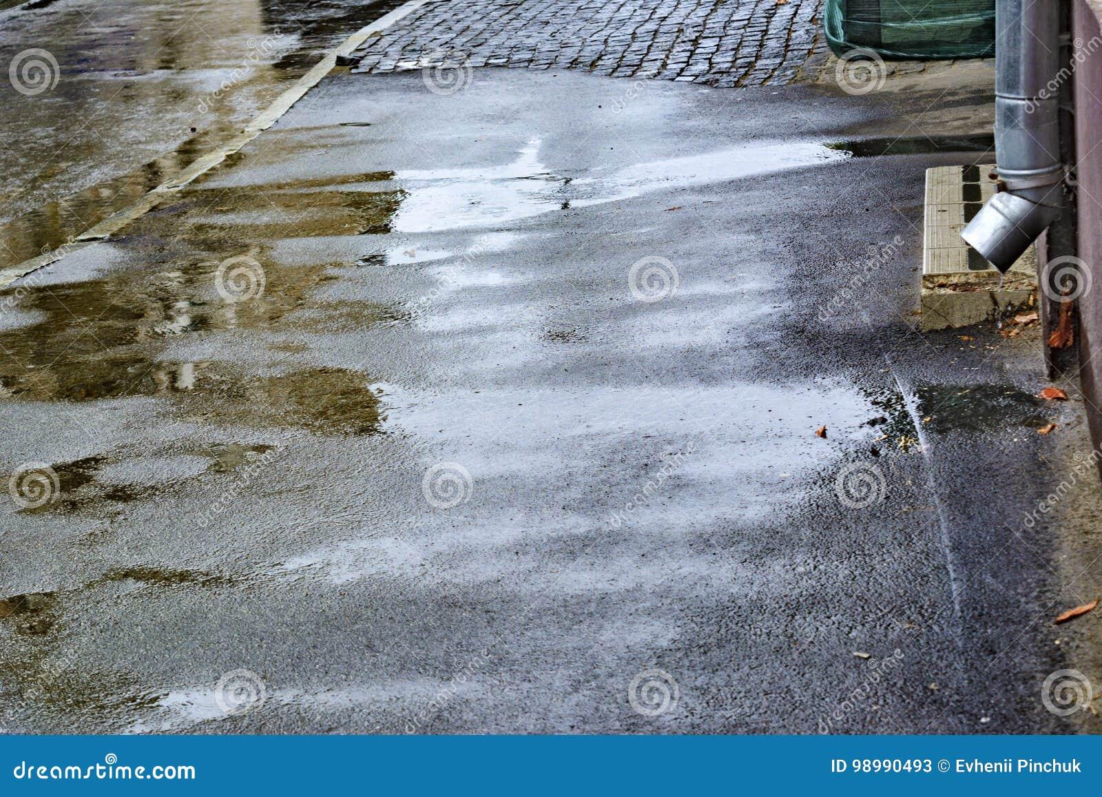 De regen van de zomer Dalende regen regendruppels Vulklei met bellen op de bestrating Nat asfalt Slecht weer Regenseizoen