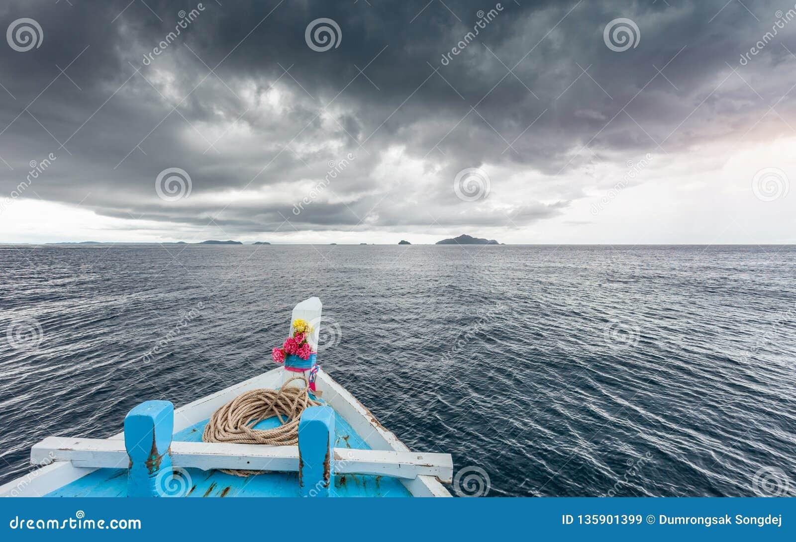 De reizende boot gaat naar eiland terwijl het regenen strom dichtbij komt