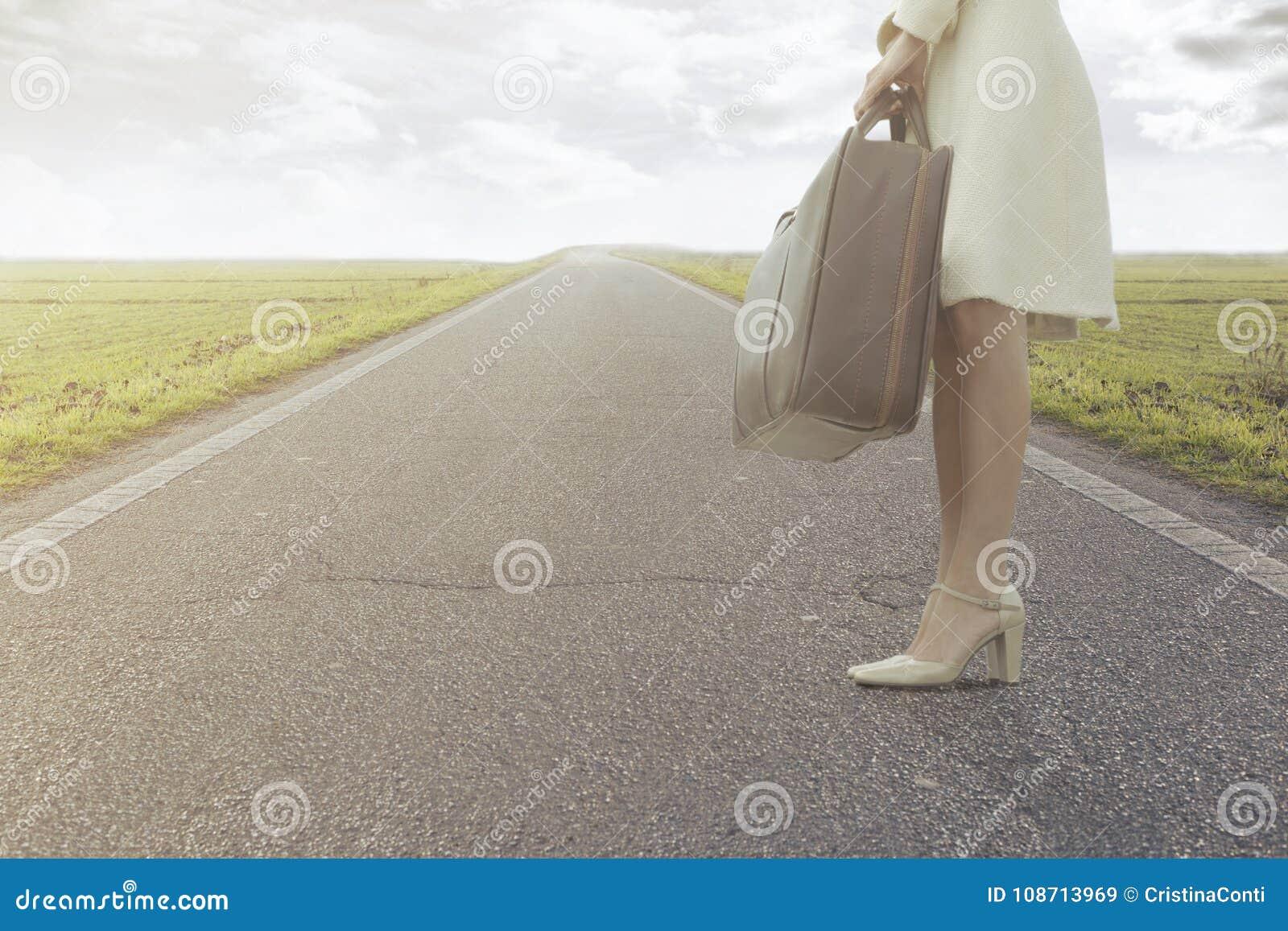 De reizende vrouw wacht met haar koffer om voor een nieuwe reis weg te gaan